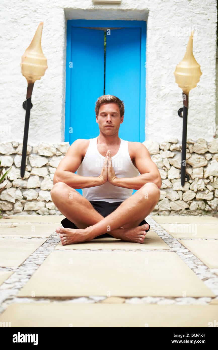 Man Meditating Outdoors At Health Spa Stock Photo