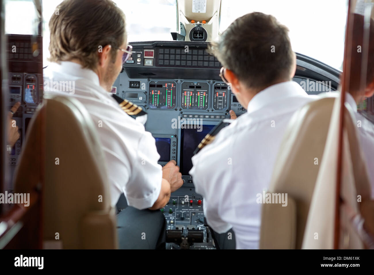 Pilots Operating Controls Of Corporate Jet - Stock Image