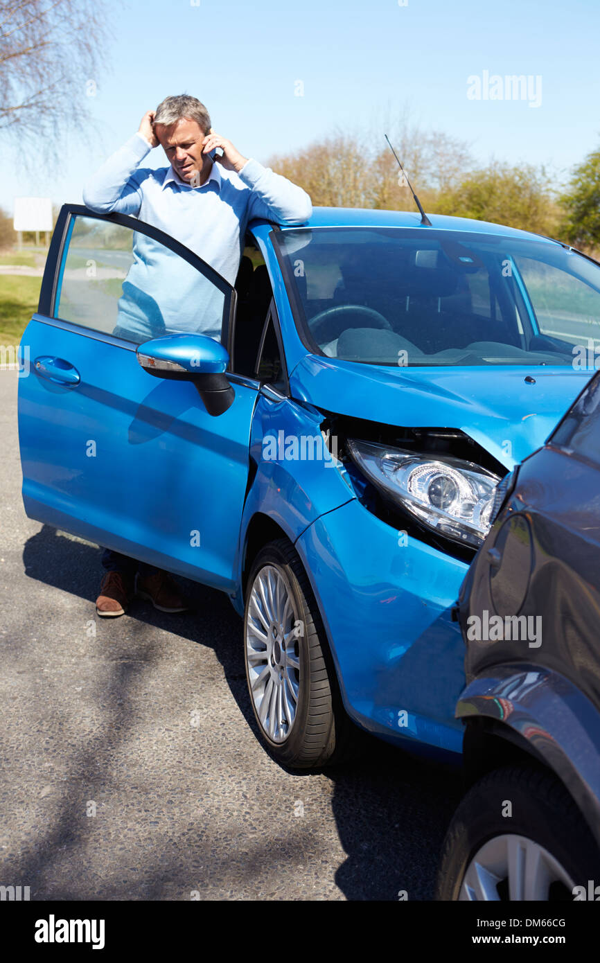 Stressed Driver Sitting At Roadside After Traffic Accident - Stock Image