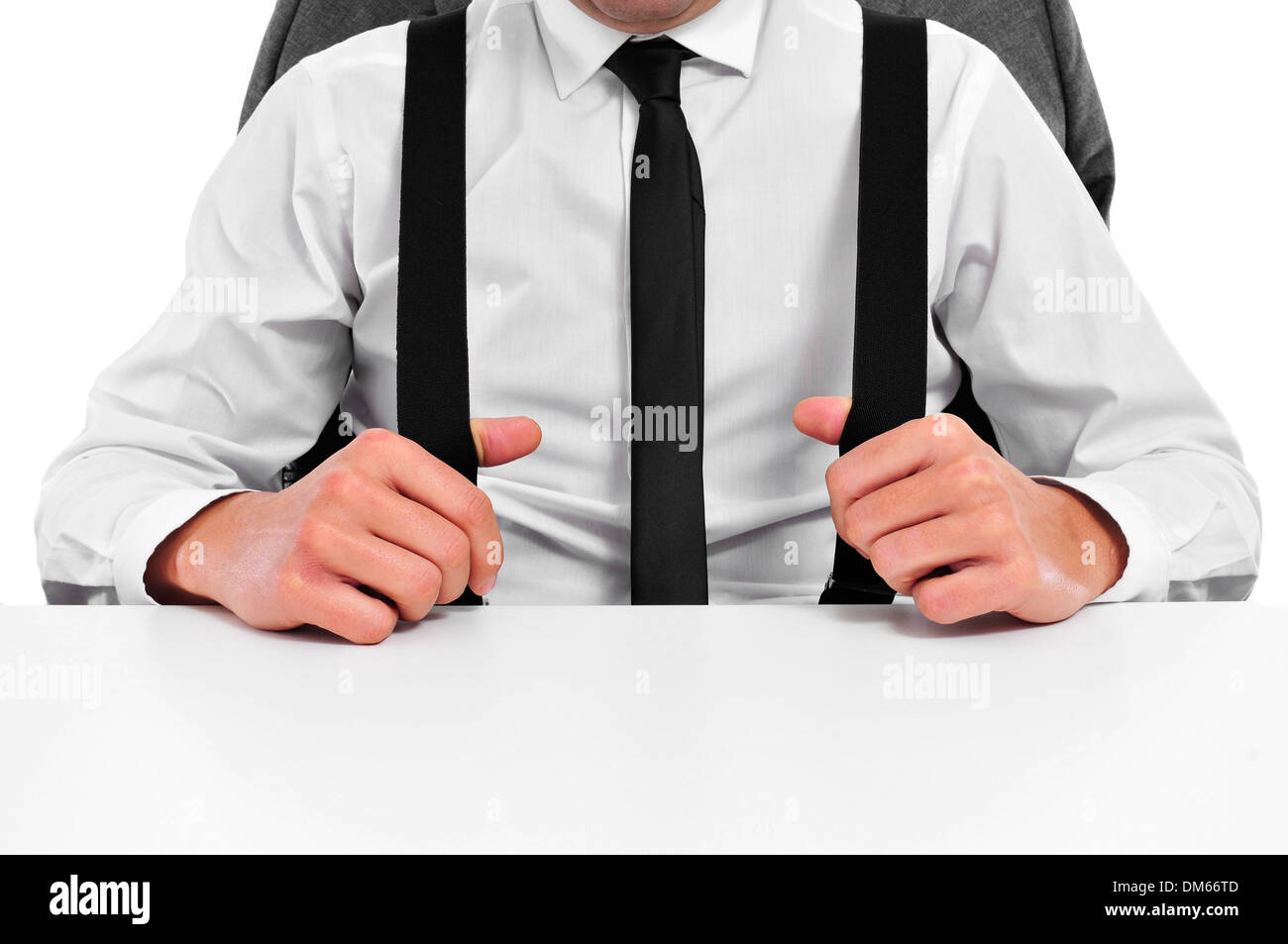 a businessman with suspenders sitting in a desk in the office - Stock Image