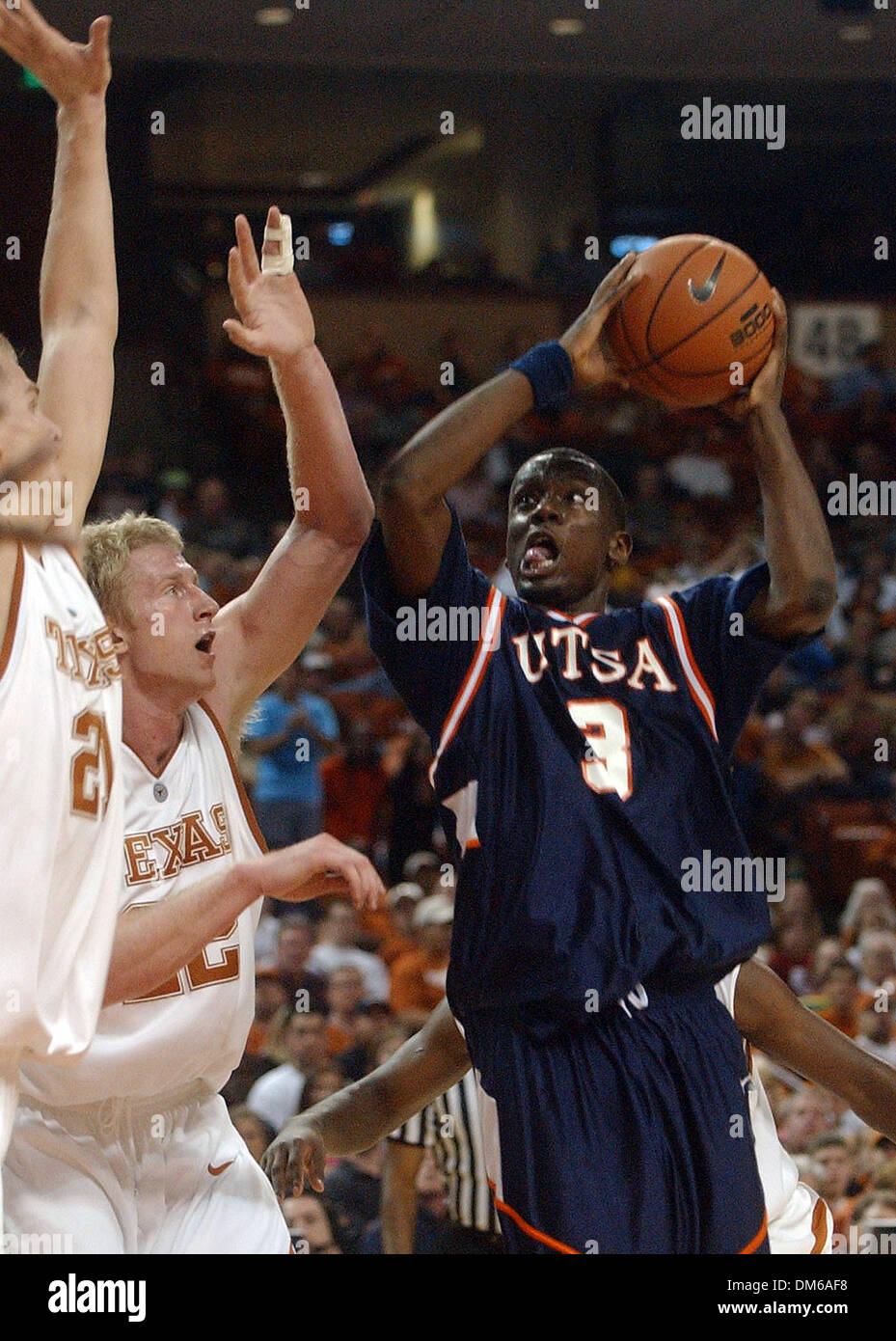 Dec 29, 2004; SAN ANTONIO, TX, USA; NCAA College Basketball: San Antonio's Andre Owens goes for the basket against the Texas Longhorns' Jason Klotz, from left, and Brad Buckman during the first half of their game at The Frank Erwin Center in Austin on Wednesday, December 29, 2004. Lisa Krantz/STAFF - Stock Image
