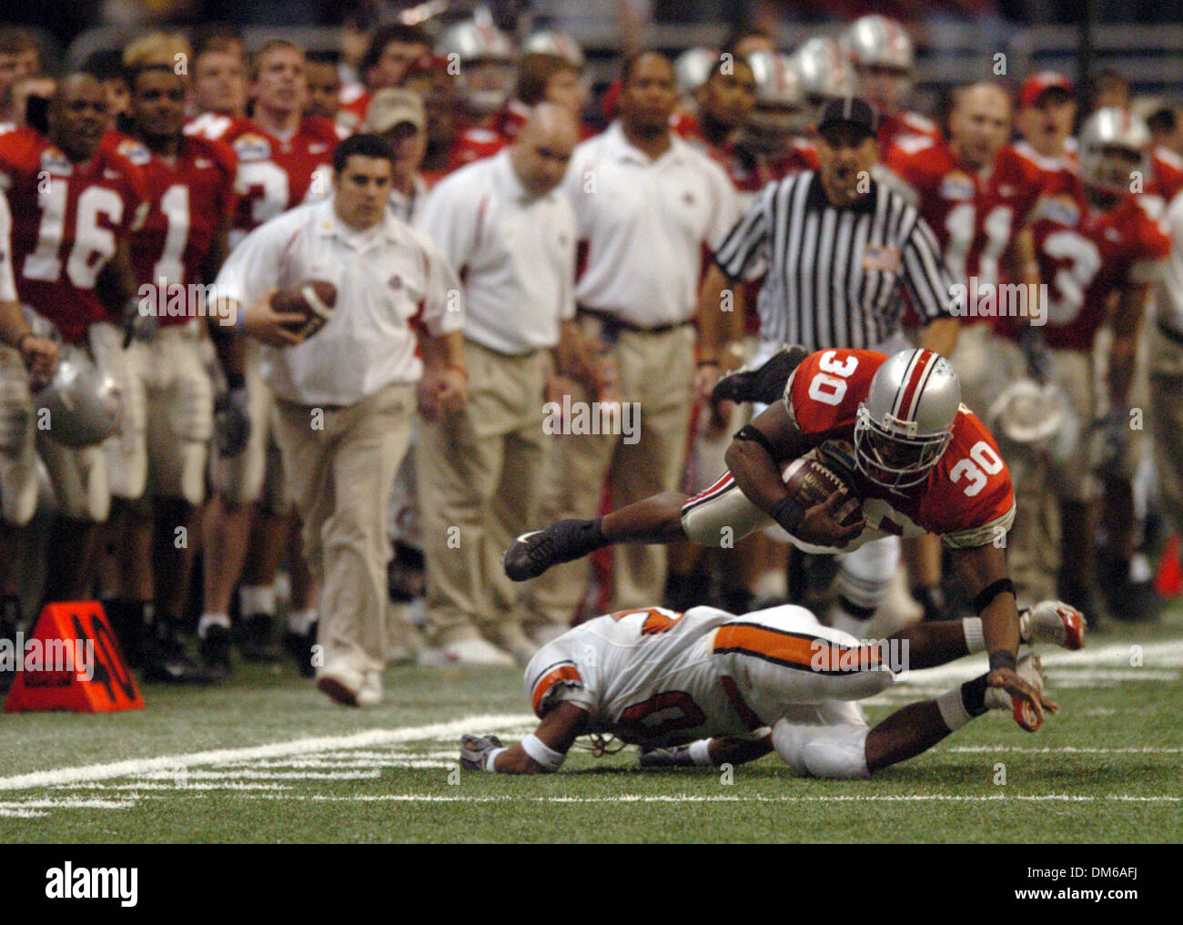 Dec 29, 2004; San Antonio, TX, USA; NCAA Football - Ohio State's running back Lydell Ross (30) gets cut down after a long run by Oklahoma State's Vernon Grant in the 3rd quarter during the 2004 MasterCard Alamo Bowl in the Alamo Dome in San Antonio. - Stock Image