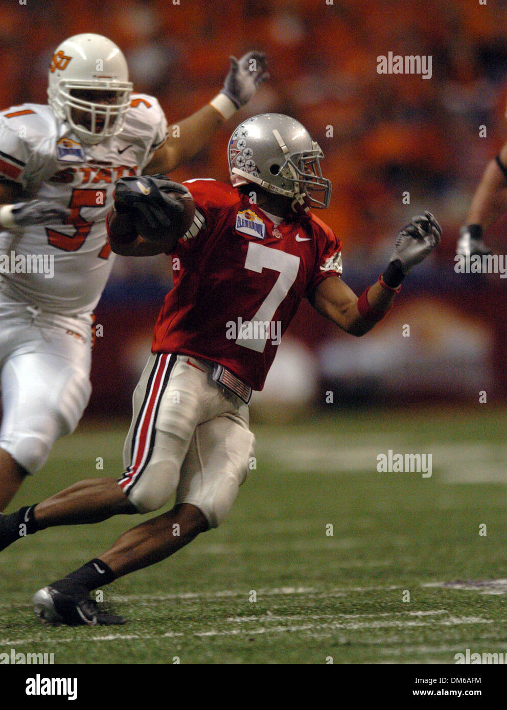 Dec 29, 2004; San Antonio, TX, USA; NCAA Football - Ohio State's Ted Ginn Jr. (7) runs in the open field pursued by Oklahoma State's Nathan Peterson (57) in the 3rd quarter during the 2004 MasterCard Alamo Bowl in the Alamo Dome in San Antonio. - Stock Image