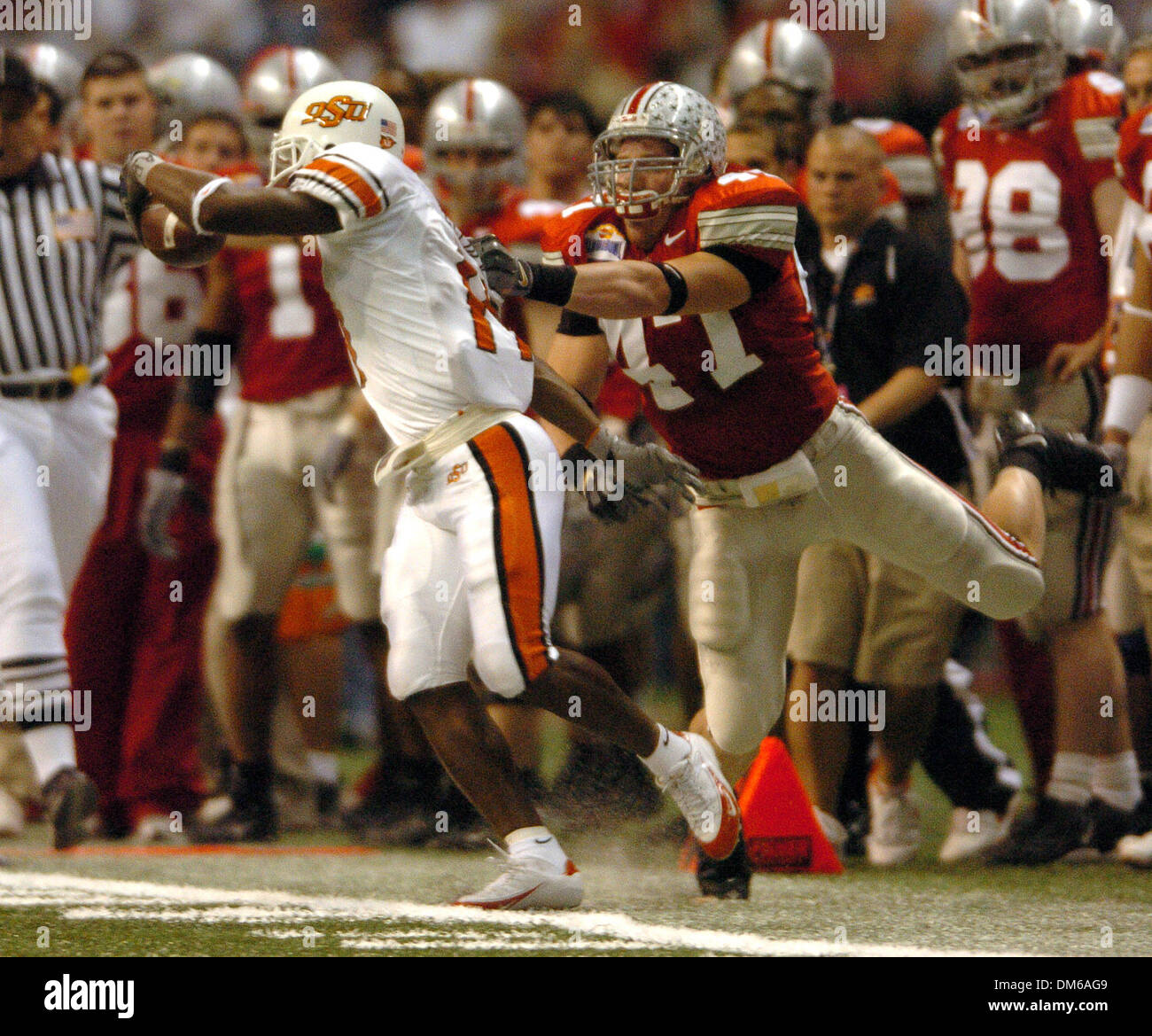 Dec 29, 2004; San Antonio, TX, USA; NCAA Football - Oklahoma State's Prentiss Elliott (11) is brought down by Ohio State's A.J. Hawk during the 2004 MasterCard Alamo Bowl at the Alamo dome in San Antonio. - Stock Image