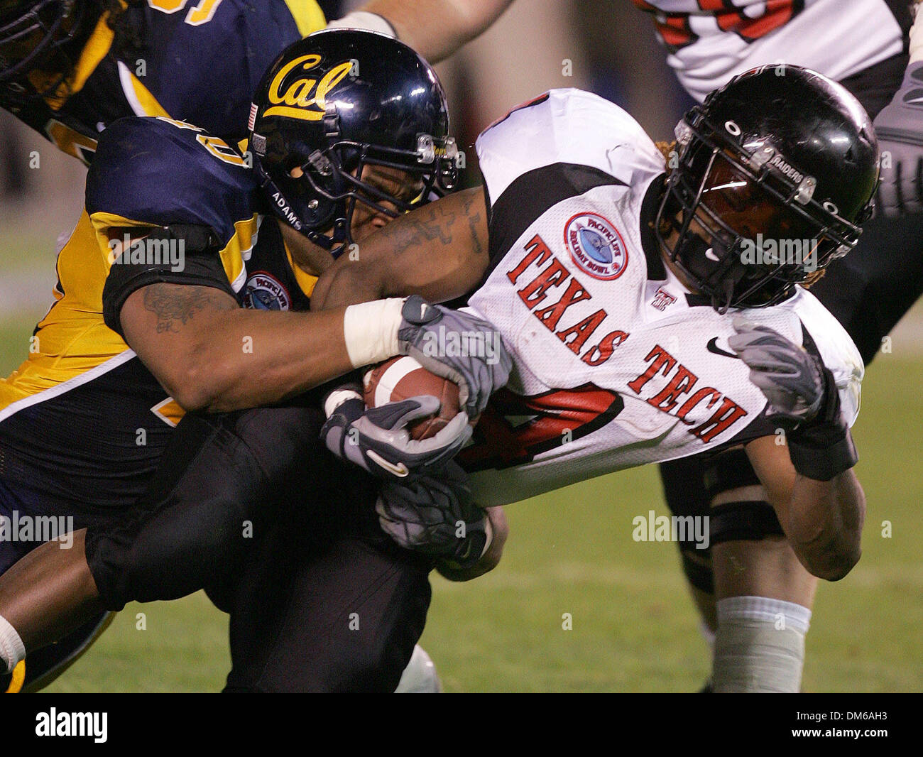Dec 30, 2004; San Diego, CA, USA; NCAA College Football (Texas Tech 45, California 31) Texas Tech's JOHNNIE MACK pushes forward Thursday night Dec 30, 2004 in San Diego during the Holiday Bowl as Cal's Wendell Hunter tries to stop him. - Stock Image