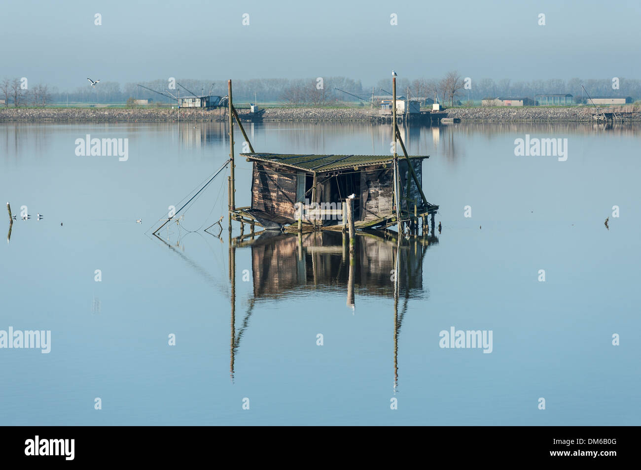 Dilapidated fishing hut in a lagoon, with reflections, Po River Delta, Comacchio, Emilia-Romagna, Italy - Stock Image