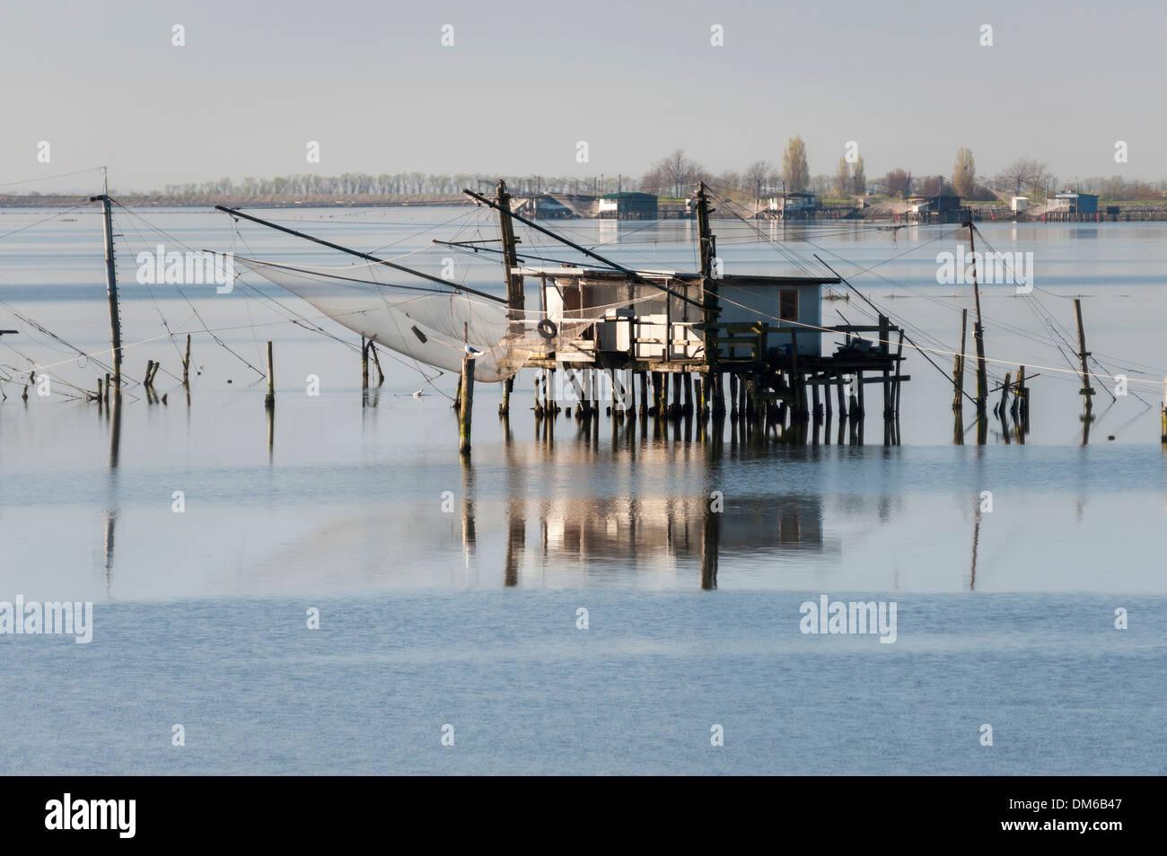 Fishing hut in a lagoon, with reflections, Po River Delta, Comacchio, Emilia-Romagna, Italy - Stock Image