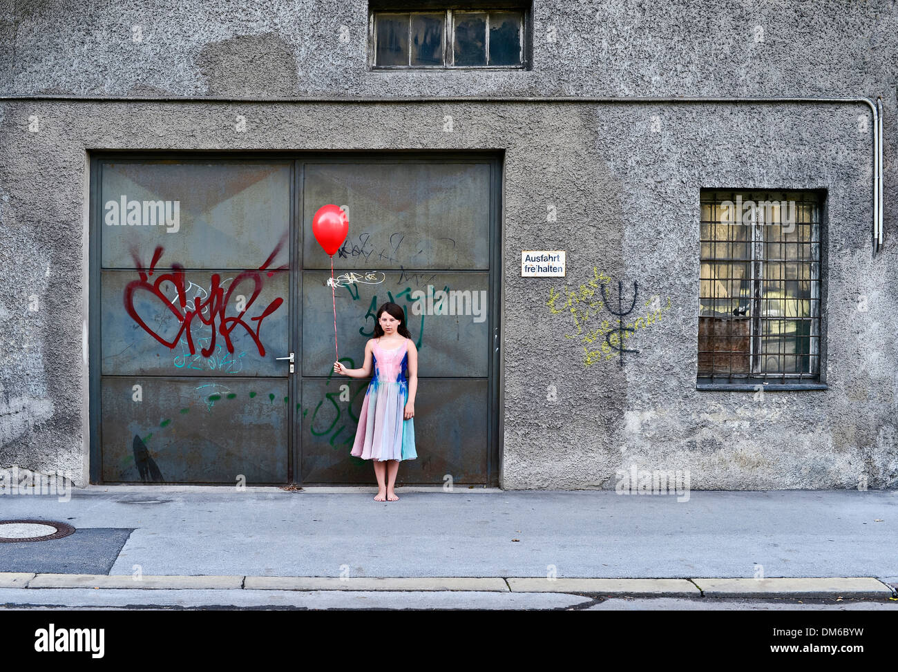 Sad Girl Holding A Red Balloon In Front Of An Old Garage Door Stock
