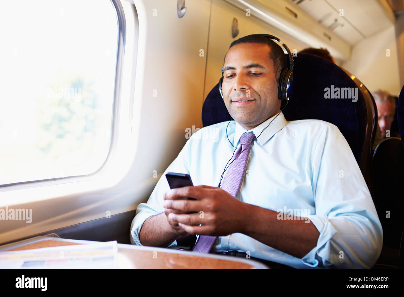 Businessman Relaxing On Train Listening To Music - Stock Image