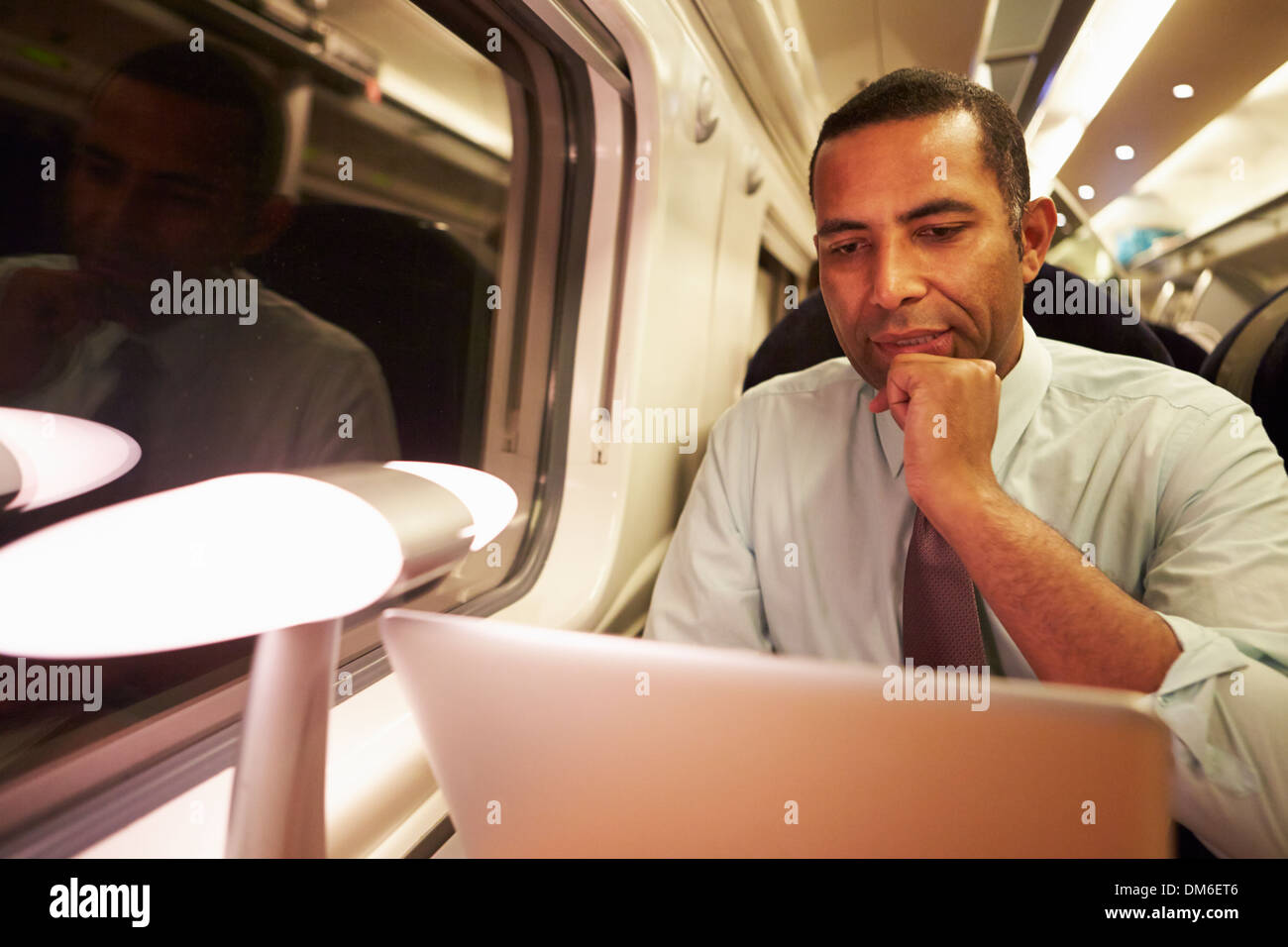 Businessman Commuting To Work On Train And Using Laptop At Night - Stock Image
