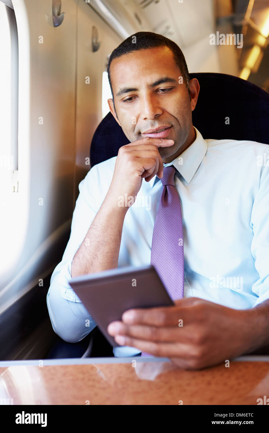 Businessman Commuting On Train Reading E Book - Stock Image