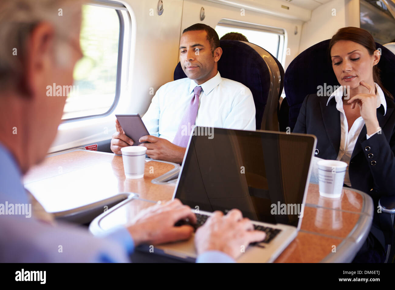 Businessman Commuting To Work On Train And Using Laptop - Stock Image