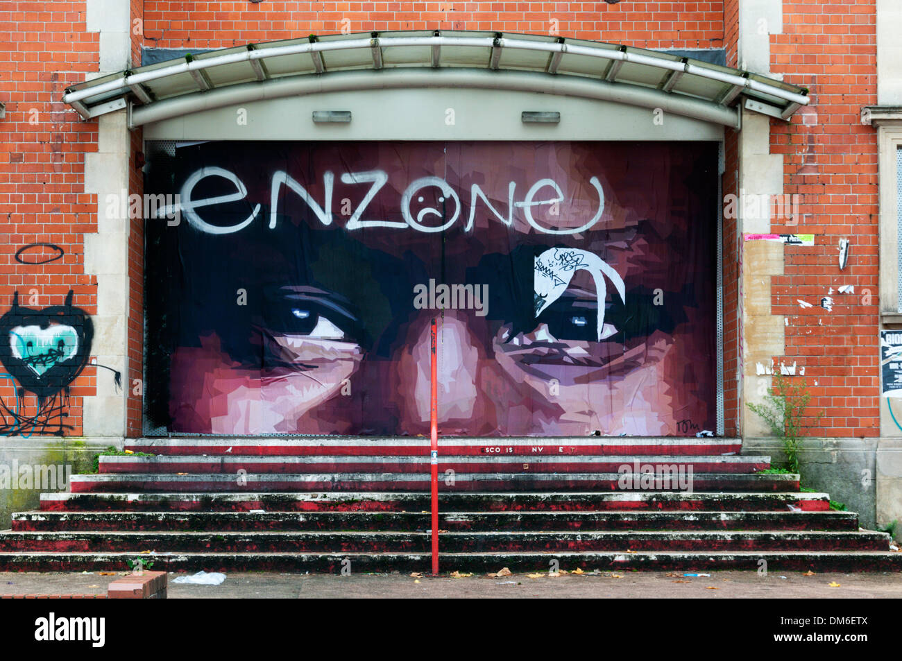 Graffiti by Tom in the Stokes Croft area of Bristol on the former cinema and Jesters Comedy Club. - Stock Image