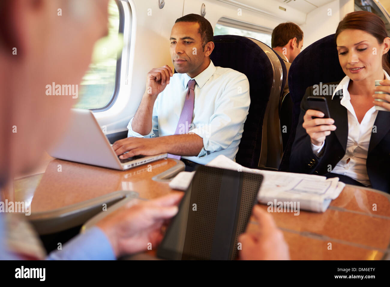 Businesspeople On Train Using Digital Devices - Stock Image