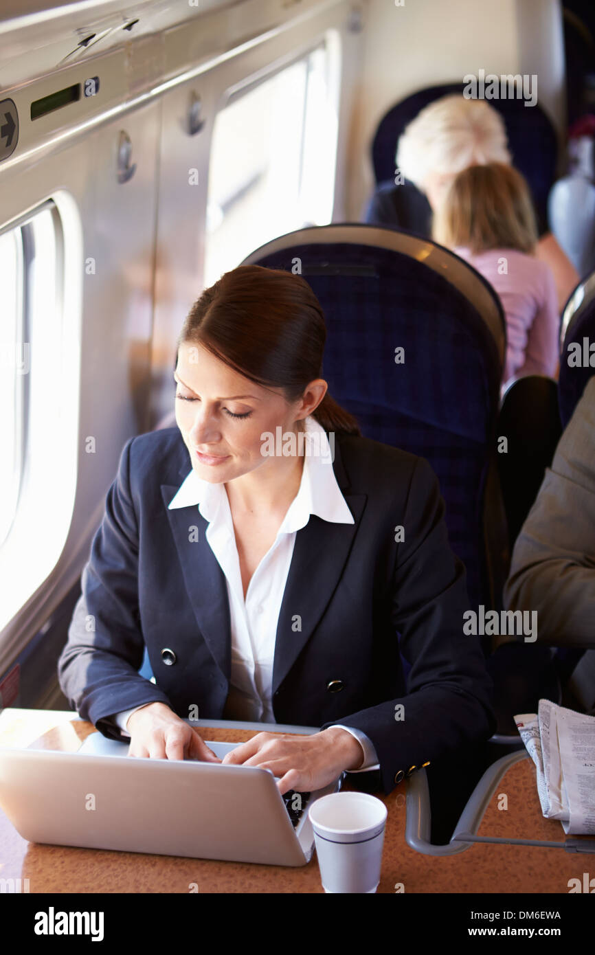 Businesswoman Commuting To Work On Train And Using Laptop - Stock Image