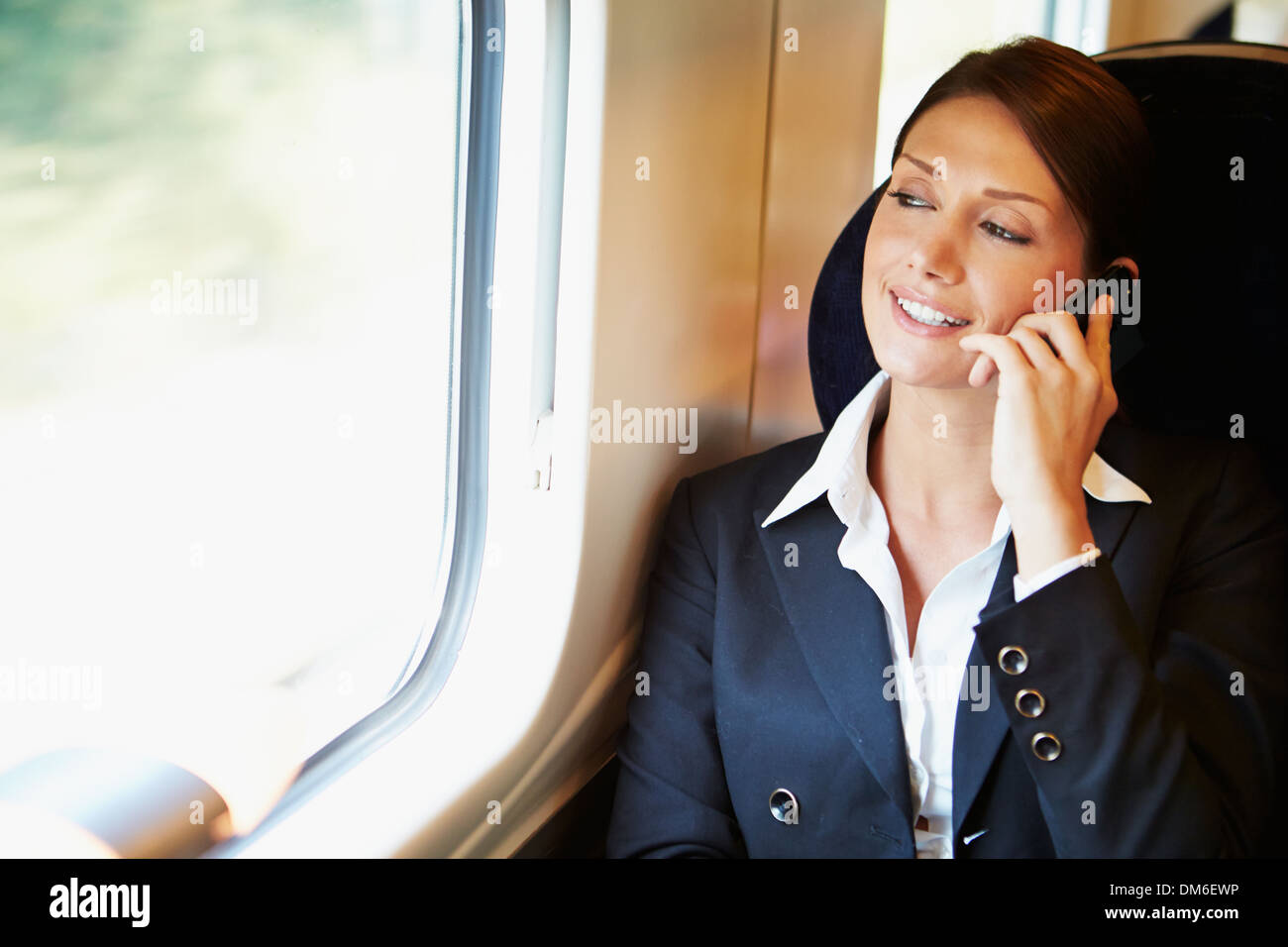 Businesswoman Commuting To Work On Train Using Mobile Phone - Stock Image