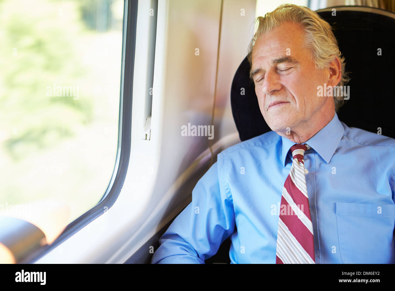 Businessman Resting On Train - Stock Image