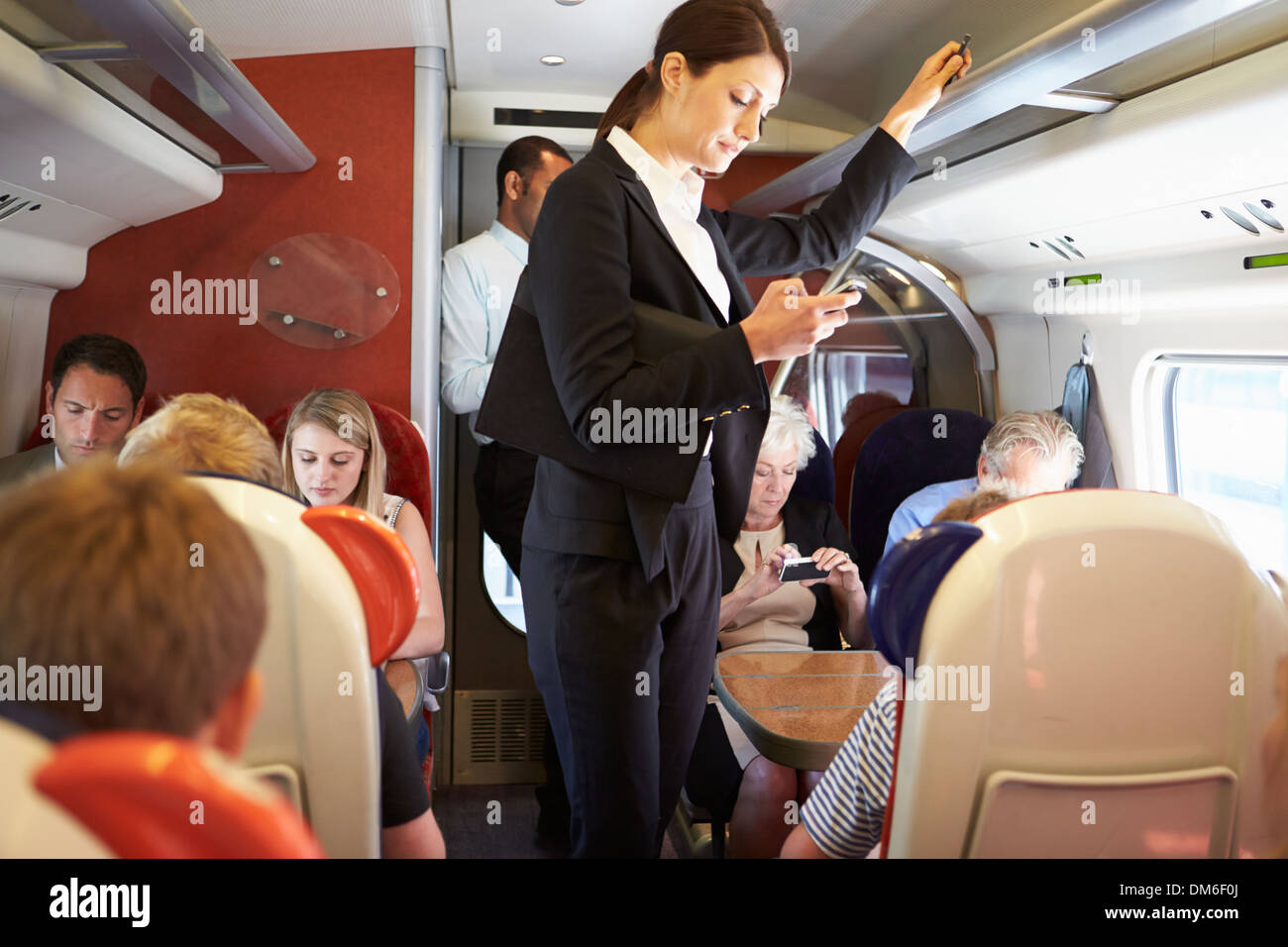 Businesswoman Using Mobile Phone On Busy Commuter Train - Stock Image
