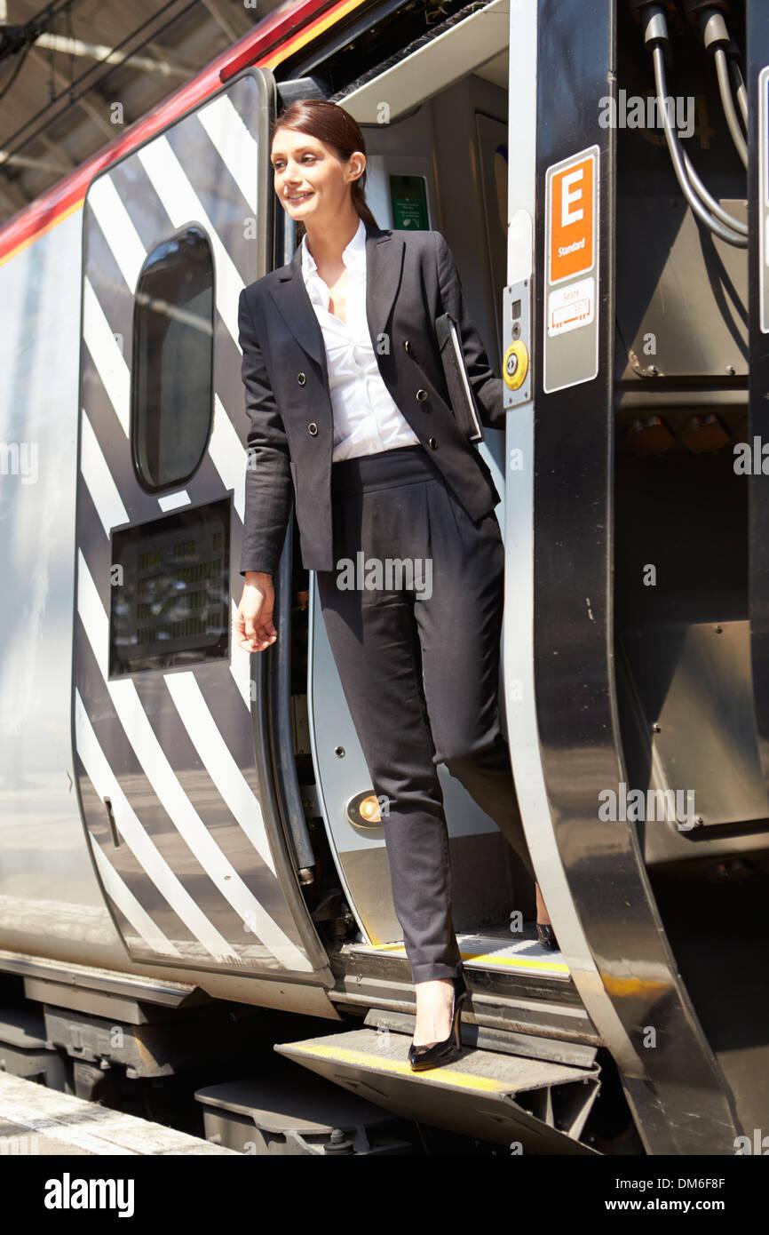 Businesswoman Getting Off Train At Platform - Stock Image