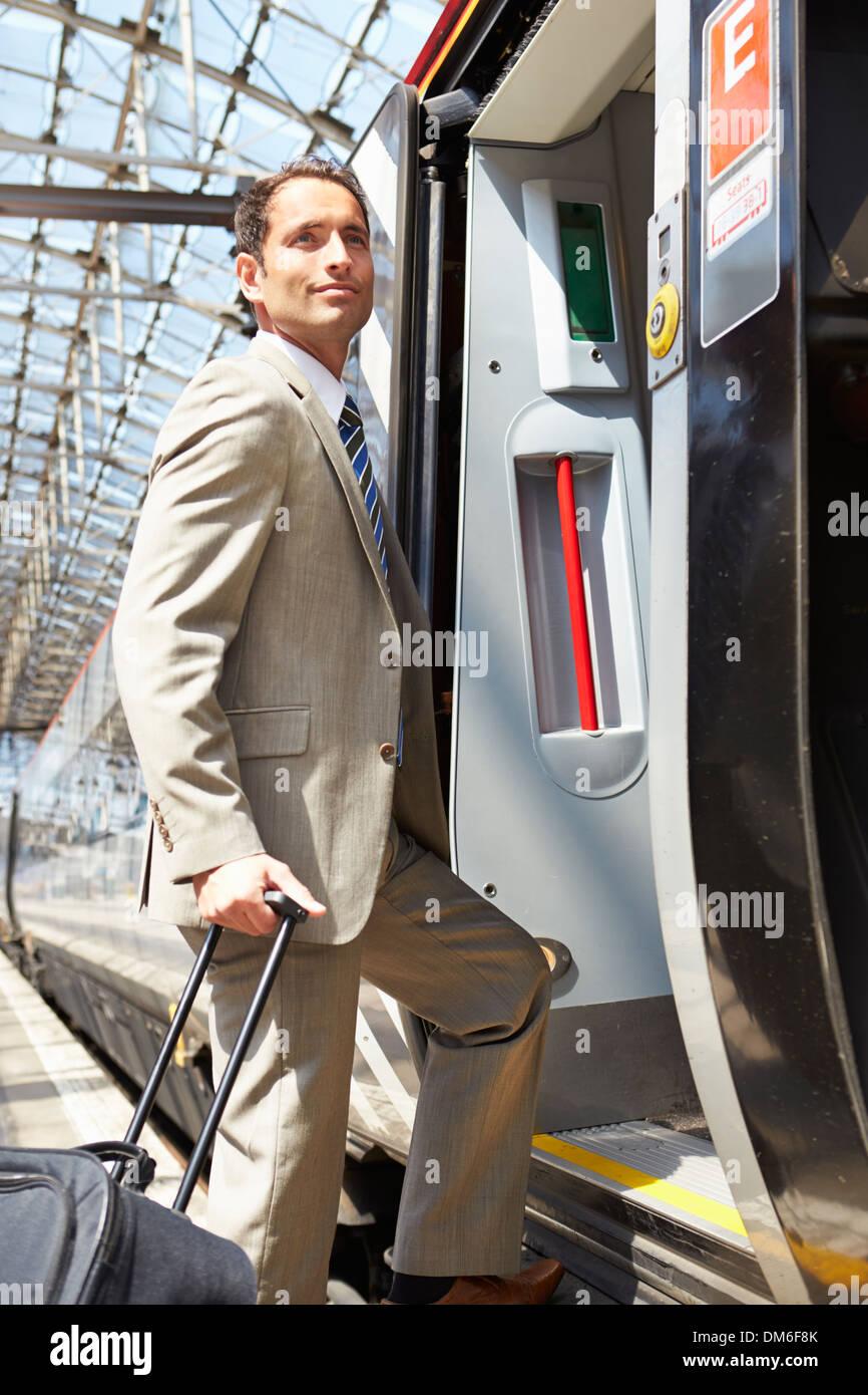 Businessman Getting On Train At Platform - Stock Image