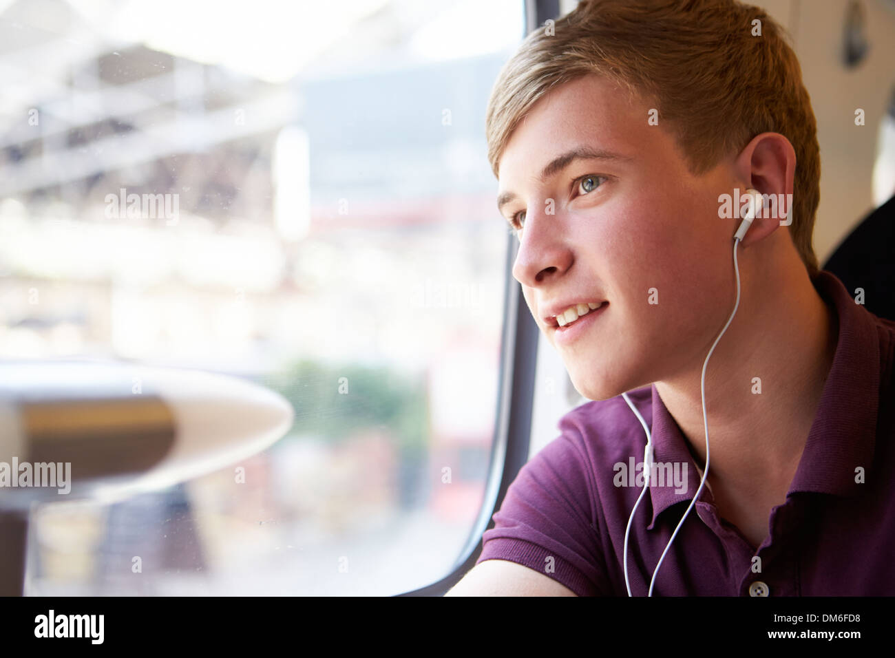 Young Man Listening To Music On Train Journey - Stock Image