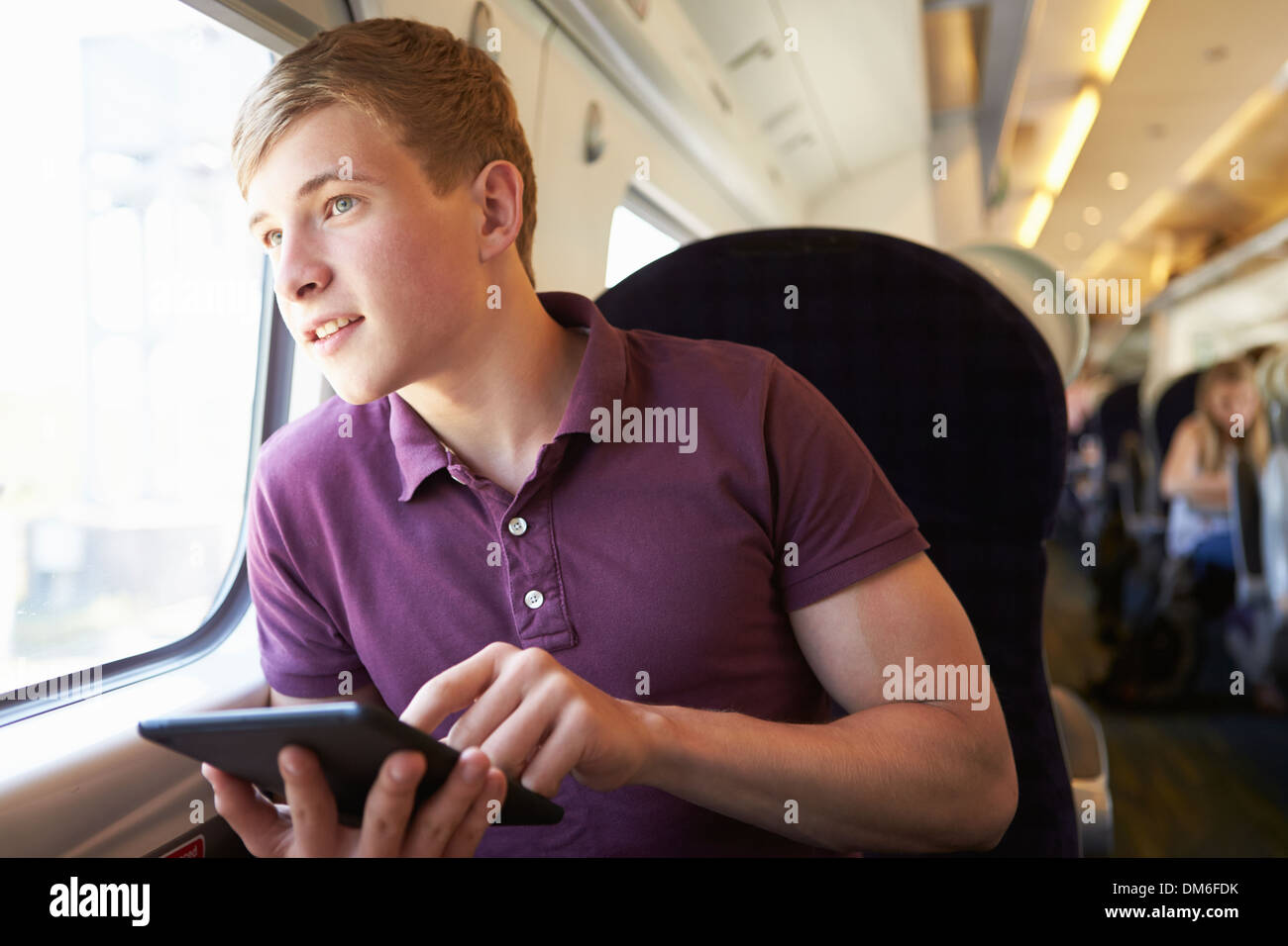 Young Man Reading E Book On Train Journey - Stock Image