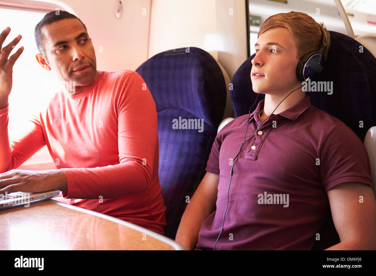 Young Man Disturbing Train Passengers With Loud Music - Stock Image