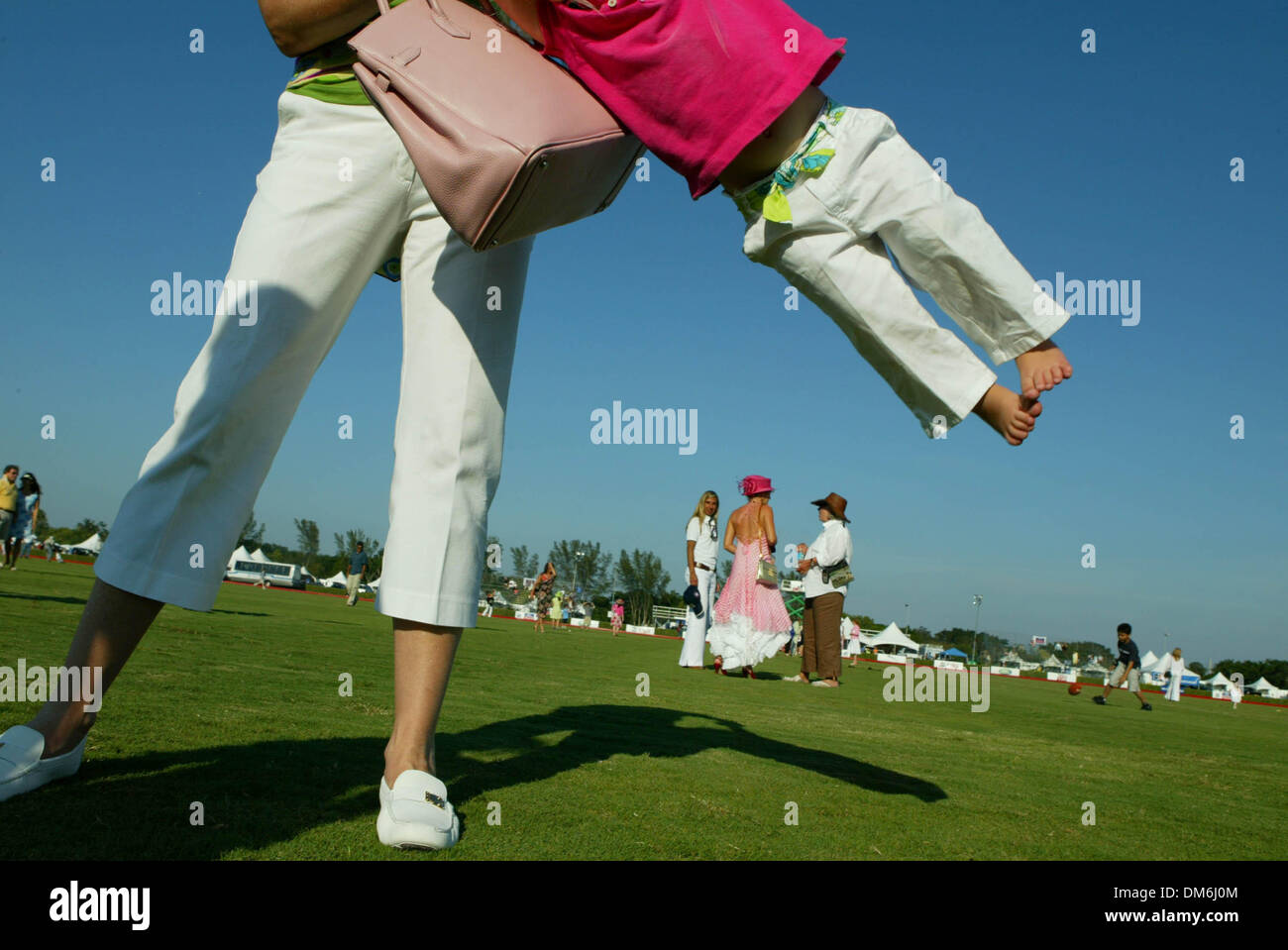 May 08, 2005; West Palm Beach, USA, USA; MARIE JOHNSON of Gulf Stream swings her daughet Lilly, 2, on the polo field during halftime at the FIP Global Cup at Royal Palm Polo in Boca Raton. Mandatory Credit: Photo by Boca Raton/Palm Beach Post/ZUMA Press. (©) Copyright 2005 by Boca Raton/Palm Beach Post - Stock Image