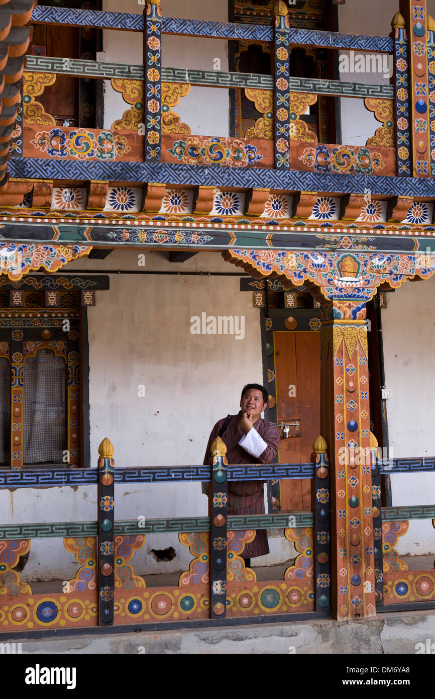 Bhutan, Bumthang Valley, Bhutanese man amongst of Nunnery decorative painted wooden structure - Stock Image