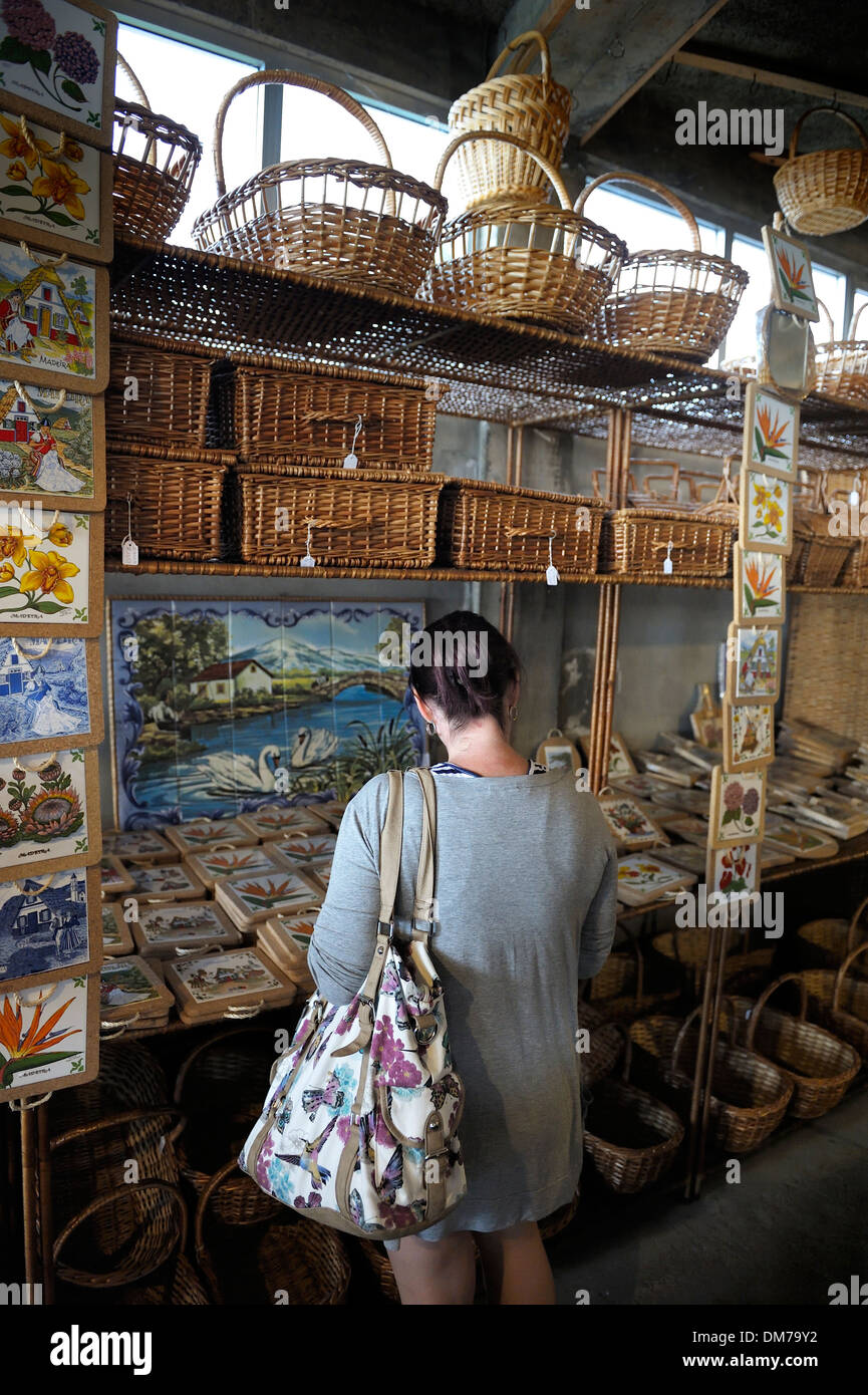 Madeira Portugal. A tourist looking at souvenirs in a wicker factory shop in Camacha - Stock Image