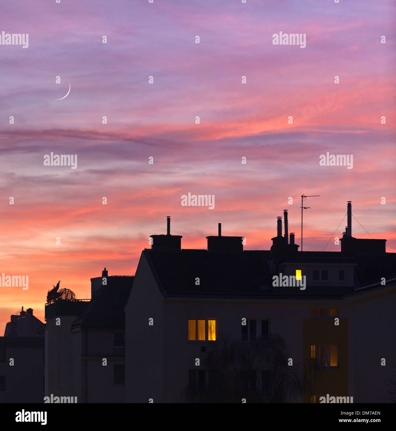Sunset over urban rooftops with lights from some home windows - Stock Image