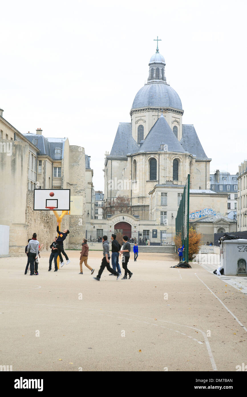 teenager playing basketball at sports field infront of lycee charlemagne school. paris, france, europe - Stock Image