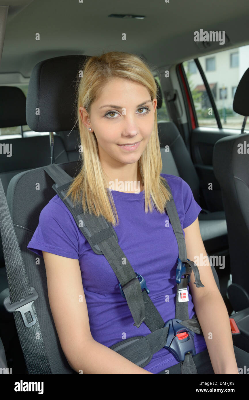 Young woman in car, restrained with a harness for persons with Stock ...