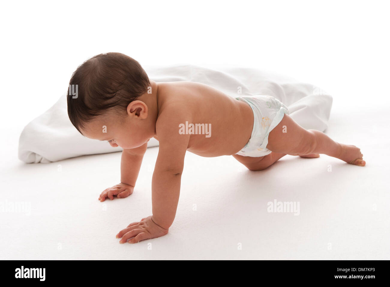 Baby boy is performing push ups on white background - Stock Image