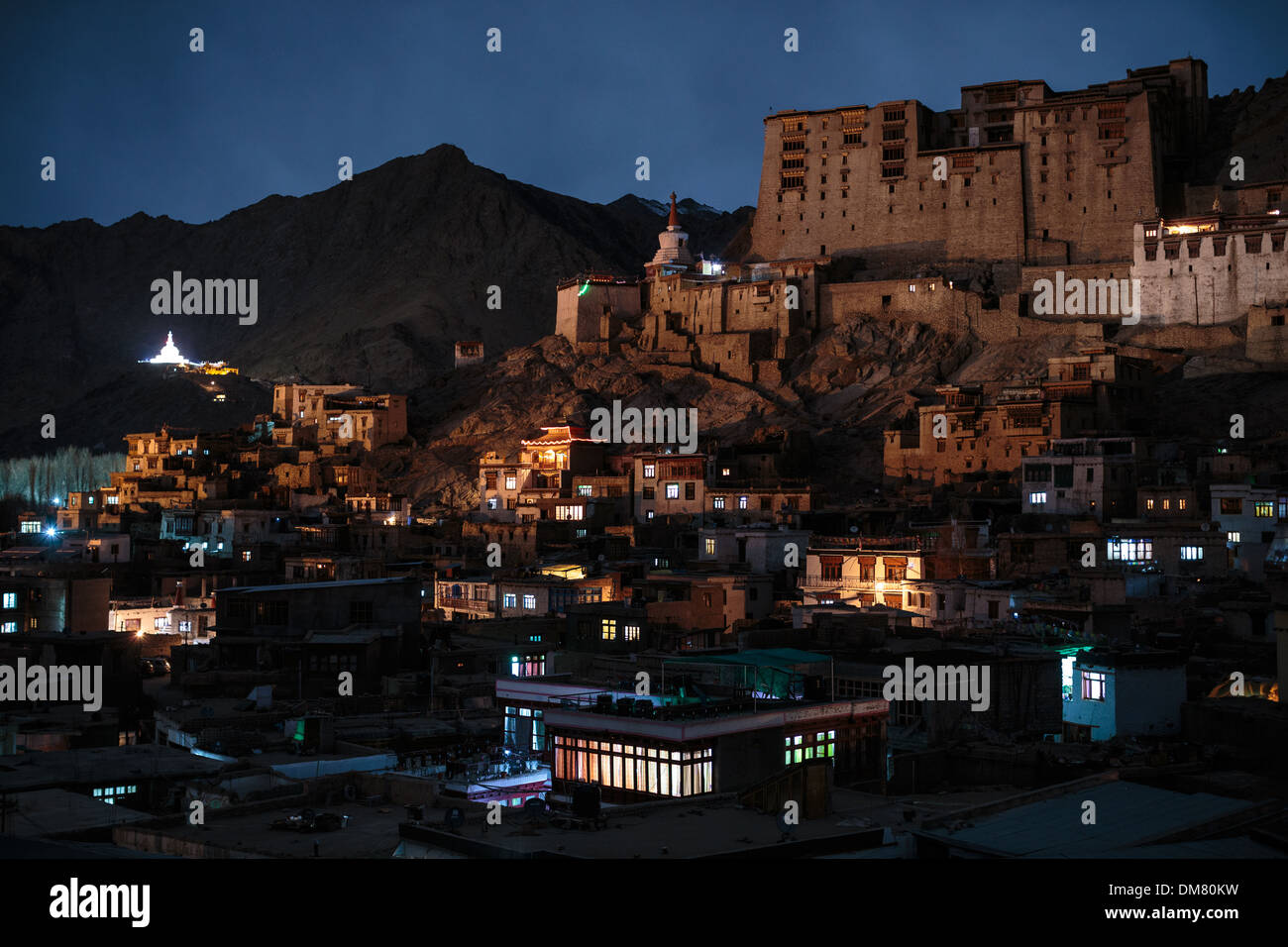Leh Palace sits over the capital city of Ladakh. Shanti Stupa shines on the himalayan mountainside. A tibetan Buddhist city in the Indus Valley India. - Stock Image