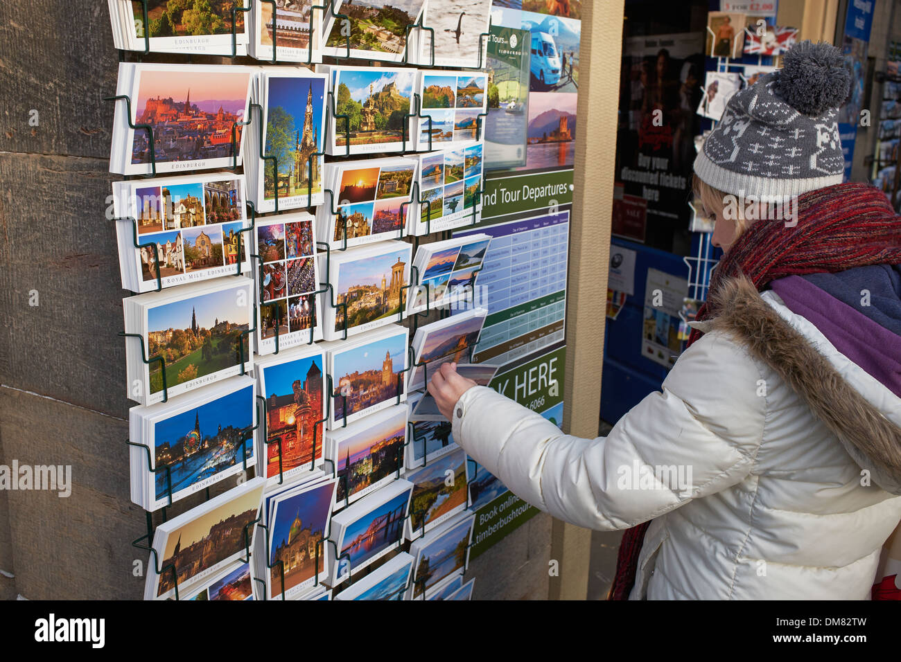 A young woman looks at postcards in Edinburgh city centre - Stock Image