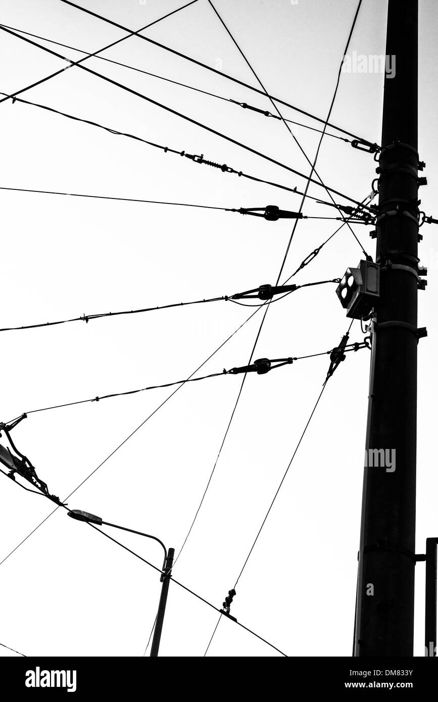 Electricity wires for the trams coming together on a large pole - Stock Image