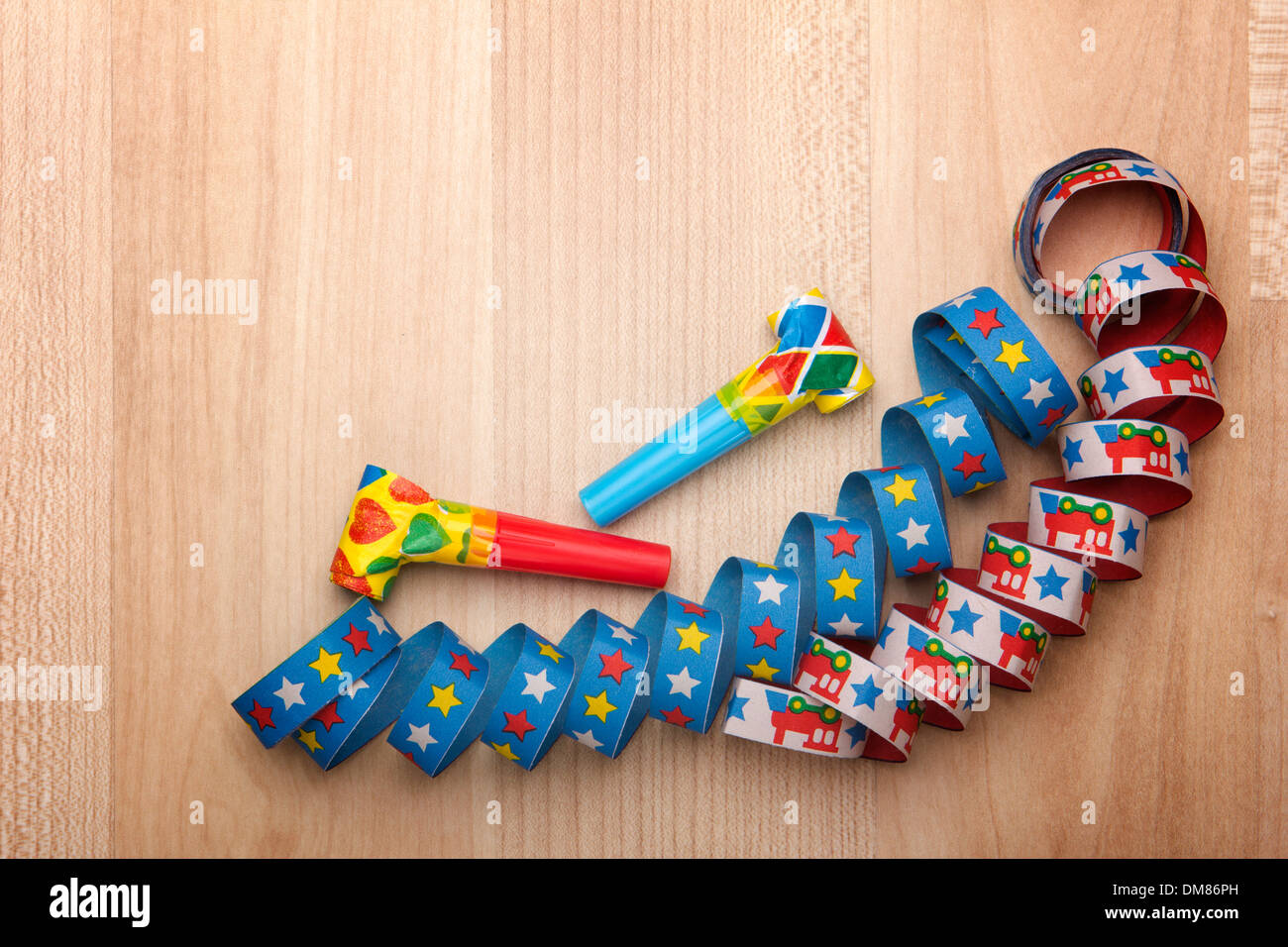 streamers and confetti as decoration for parties, sylvester with wooden background - Stock Image