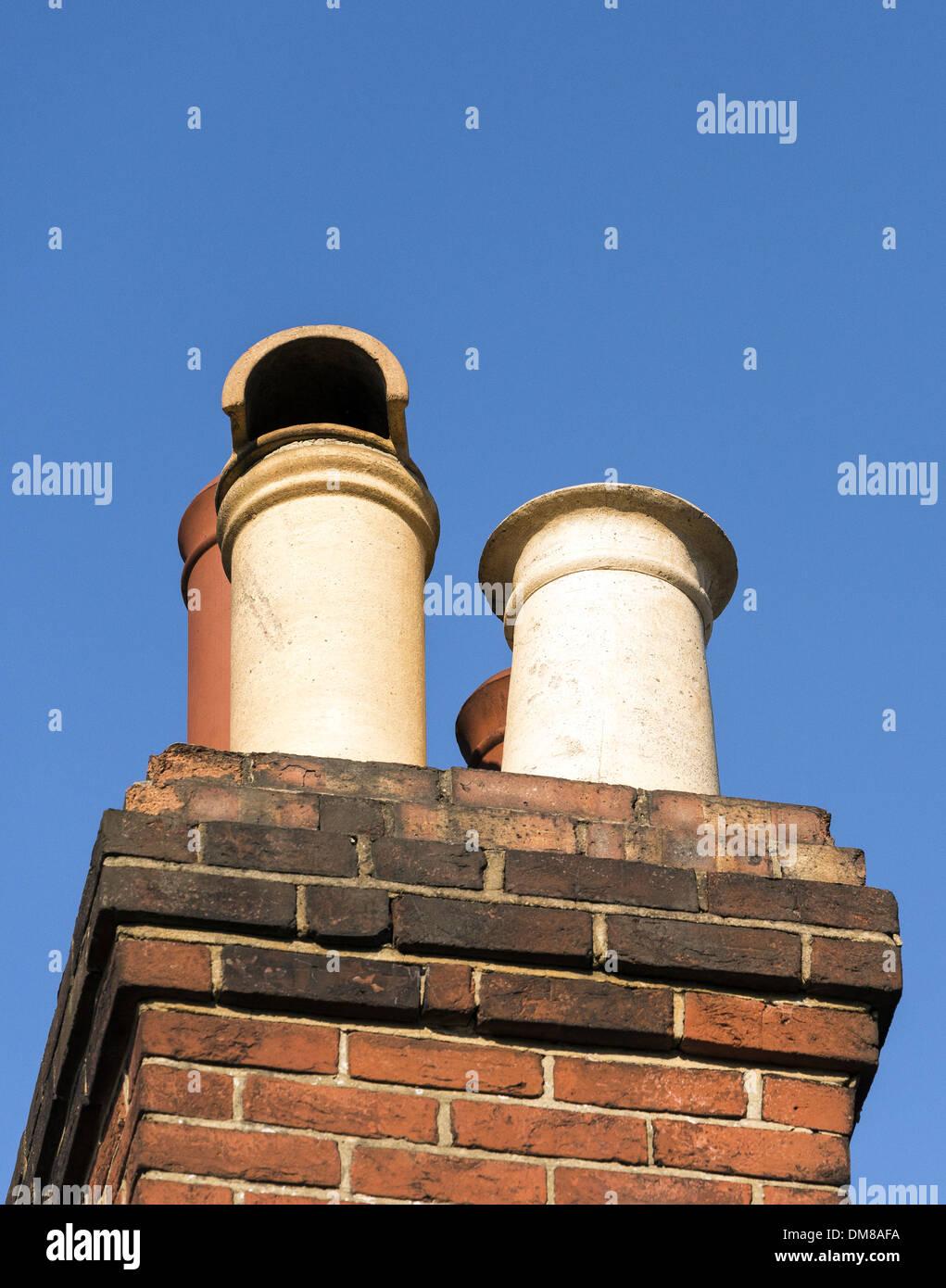 Chimney pots set against blue sky - Stock Image