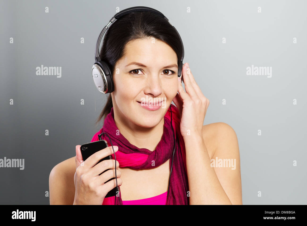 Beautiful woman in a magenta summer dress listening to music with her headphones - Stock Image