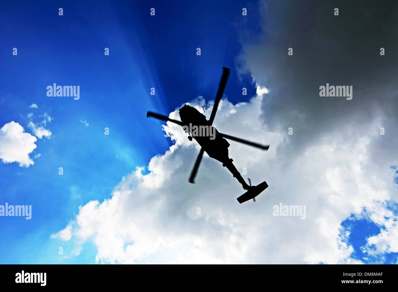 Helicopter Silhouette against clouds - Stock Image