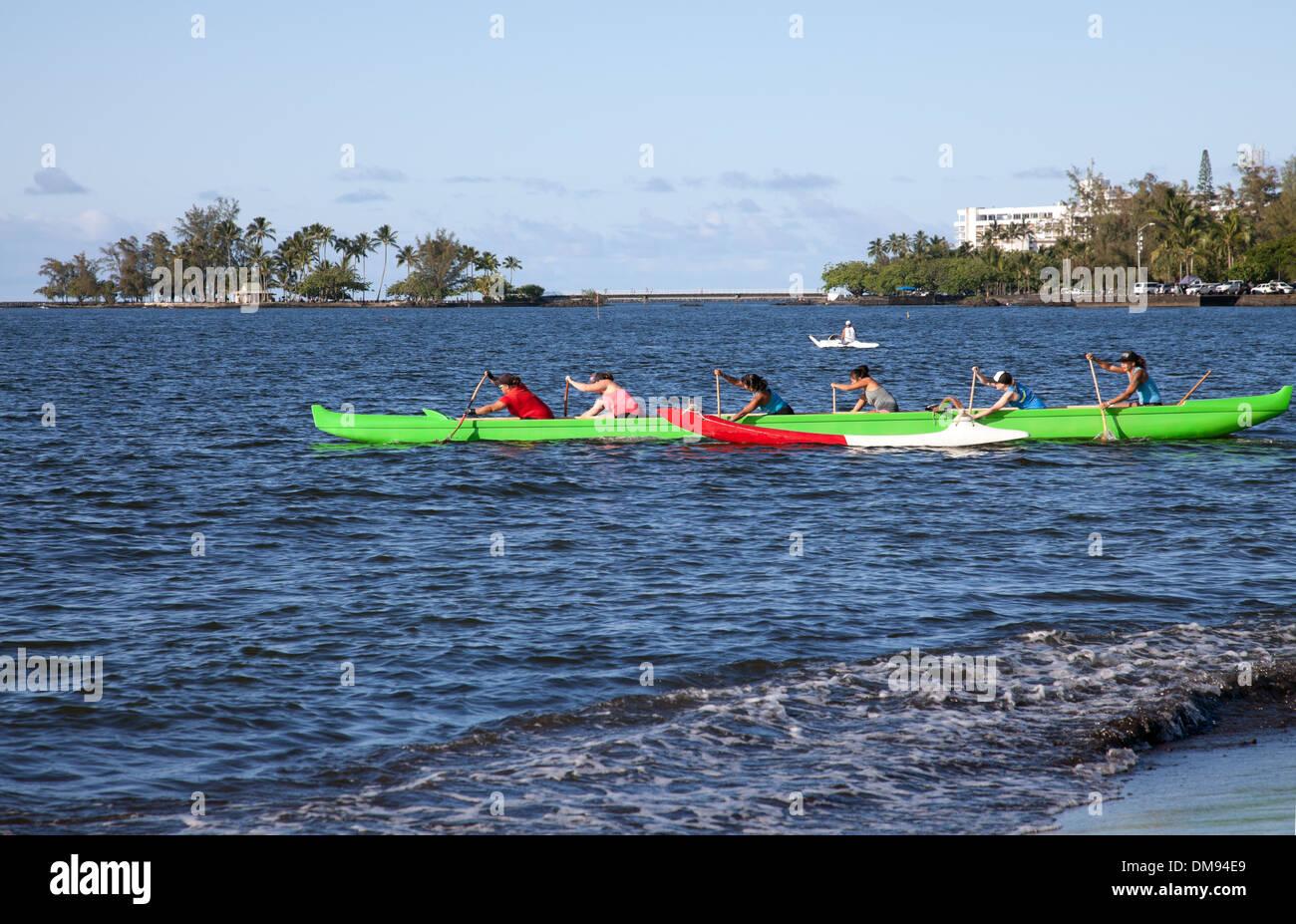 Canoe club practice races on Hilo Bay, Hawaii. - Stock Image