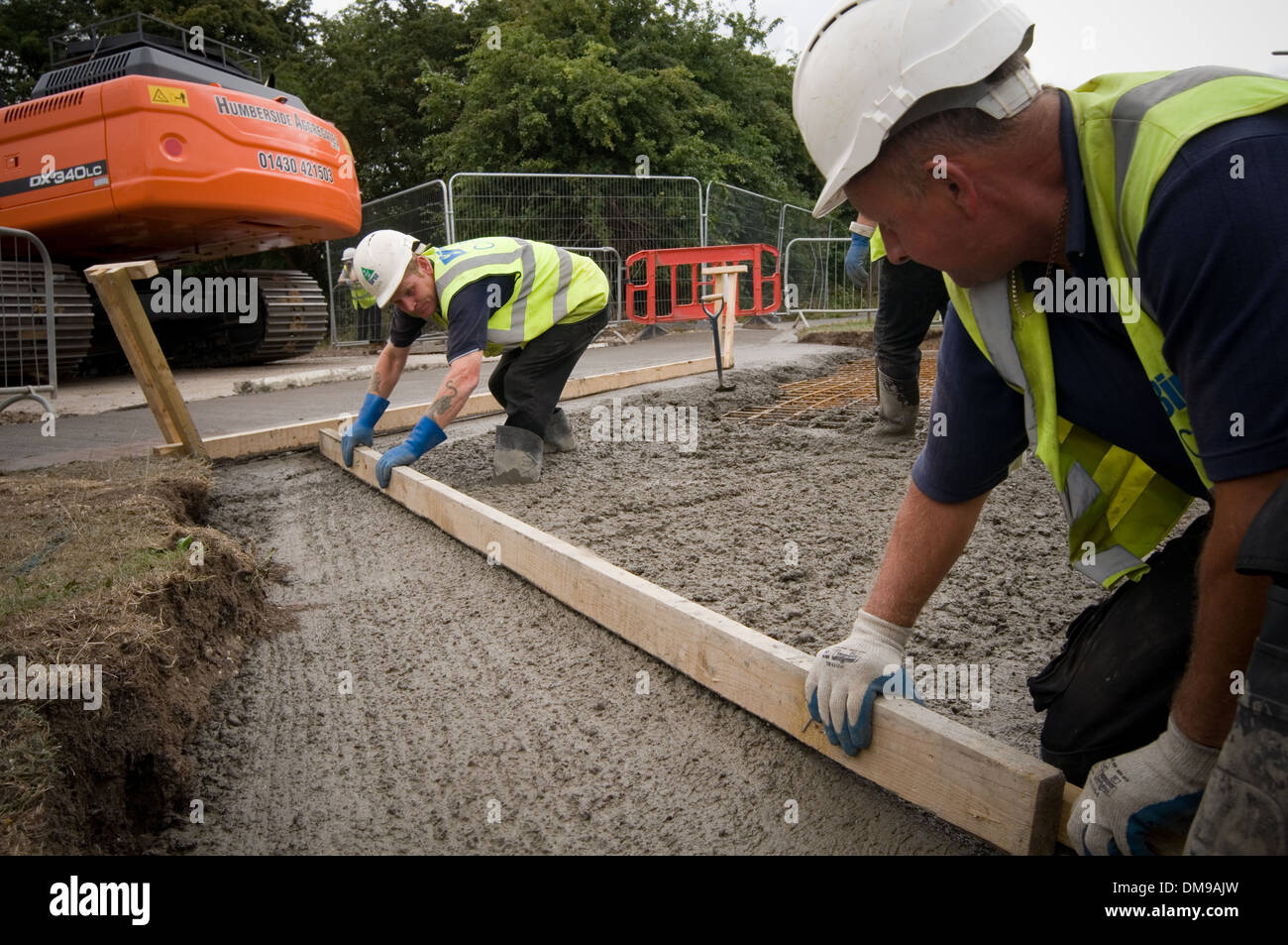 tamping concrete pour pouring pours  welly boots boot wellies construction industry groundwork foundation foundations Stock Photo