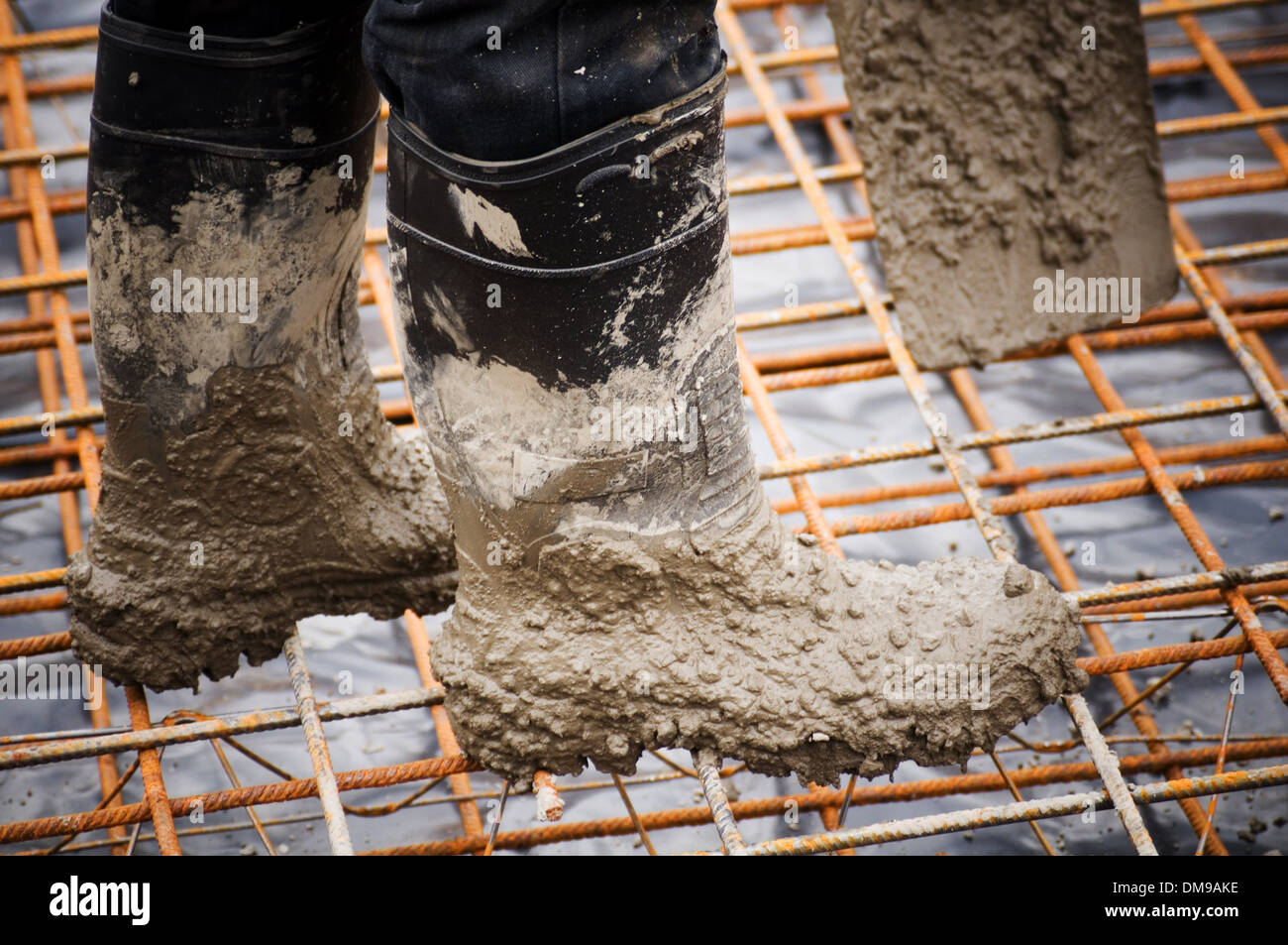 concrete pour pouring pours rebar reinforced reinforcing steel welly boots boot wellies construction industry groundwork foundat - Stock Image