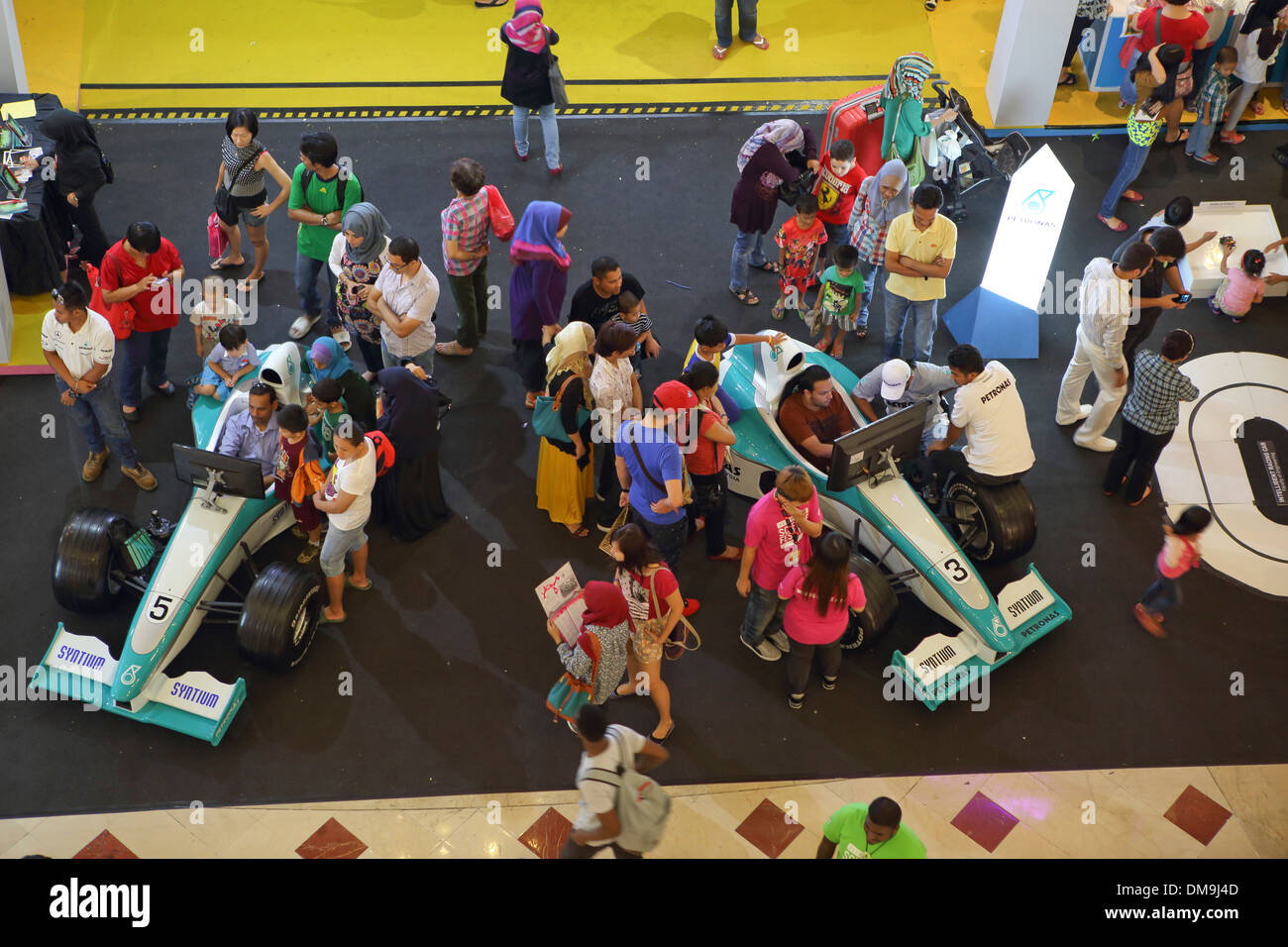 Crowd looking at Formula One Racing car display in Suria KLCC mall - Stock Image