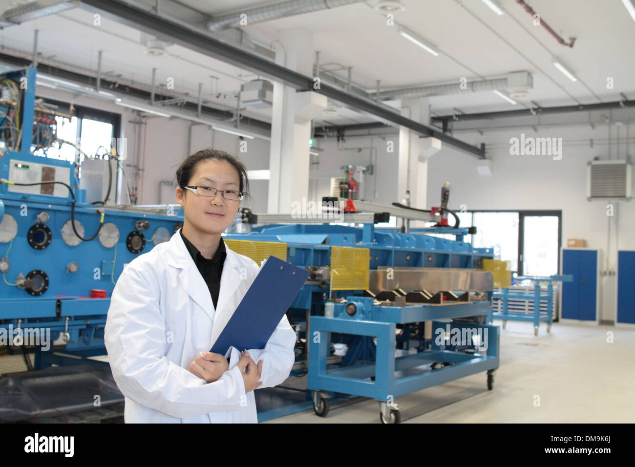 an Asia woman scientist is working in a holography lab with cleanroom coat installing new technolgy Stock Photo