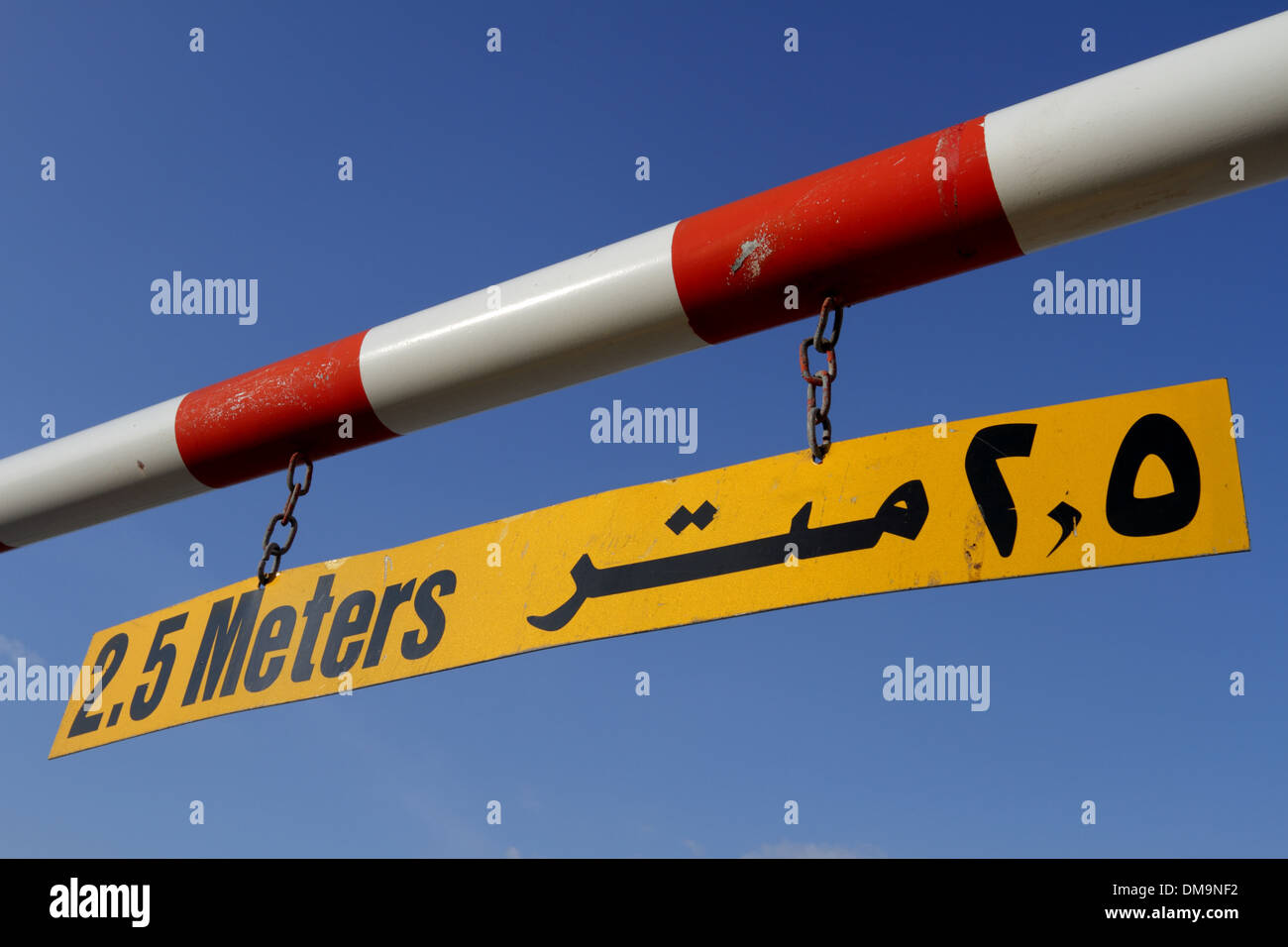 Maximum height warning sign in English and Arabic against a blue sky, Kingdom of Bahrain - Stock Image