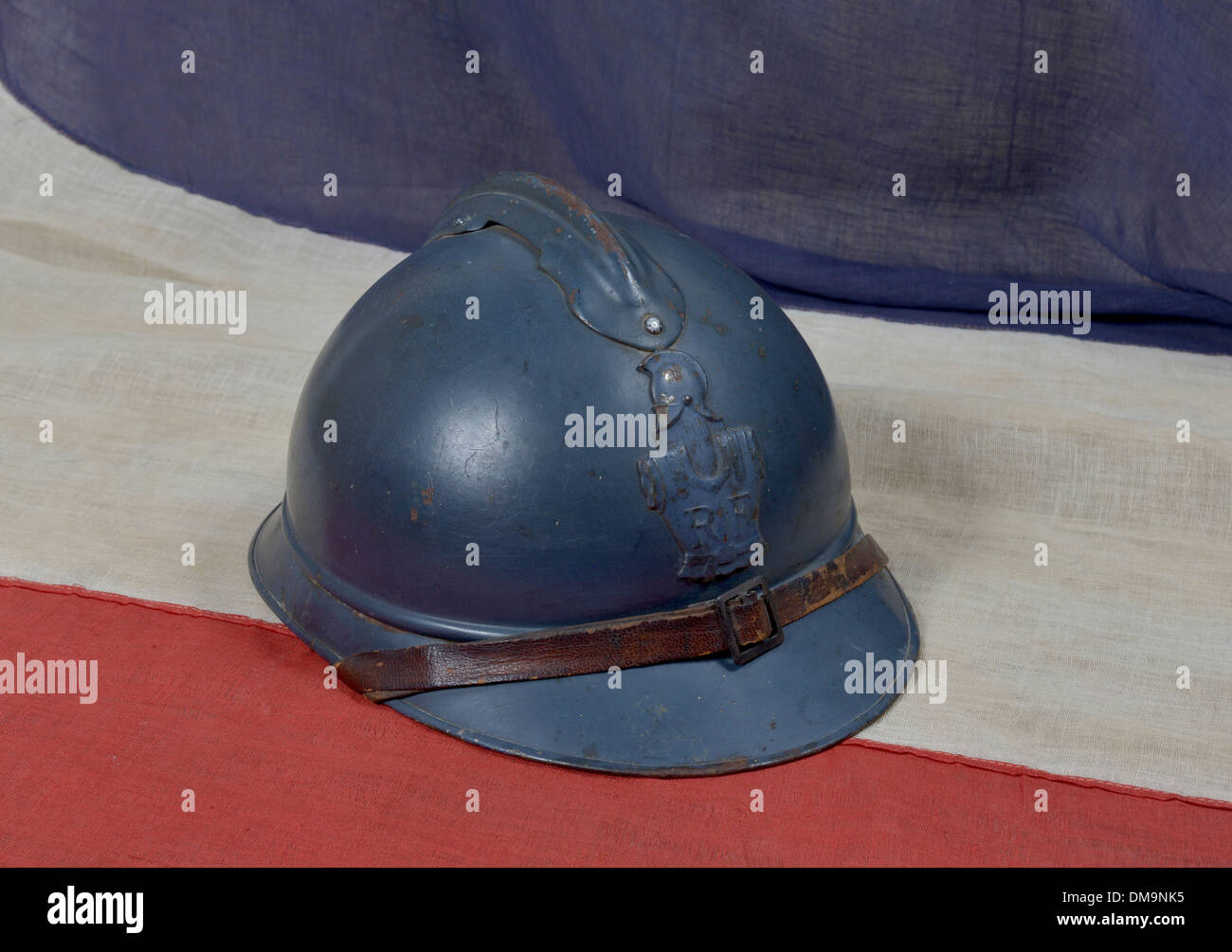 a46ea0fdcd1 french Adrian ww1 helmet on the french antique flag - Stock Image