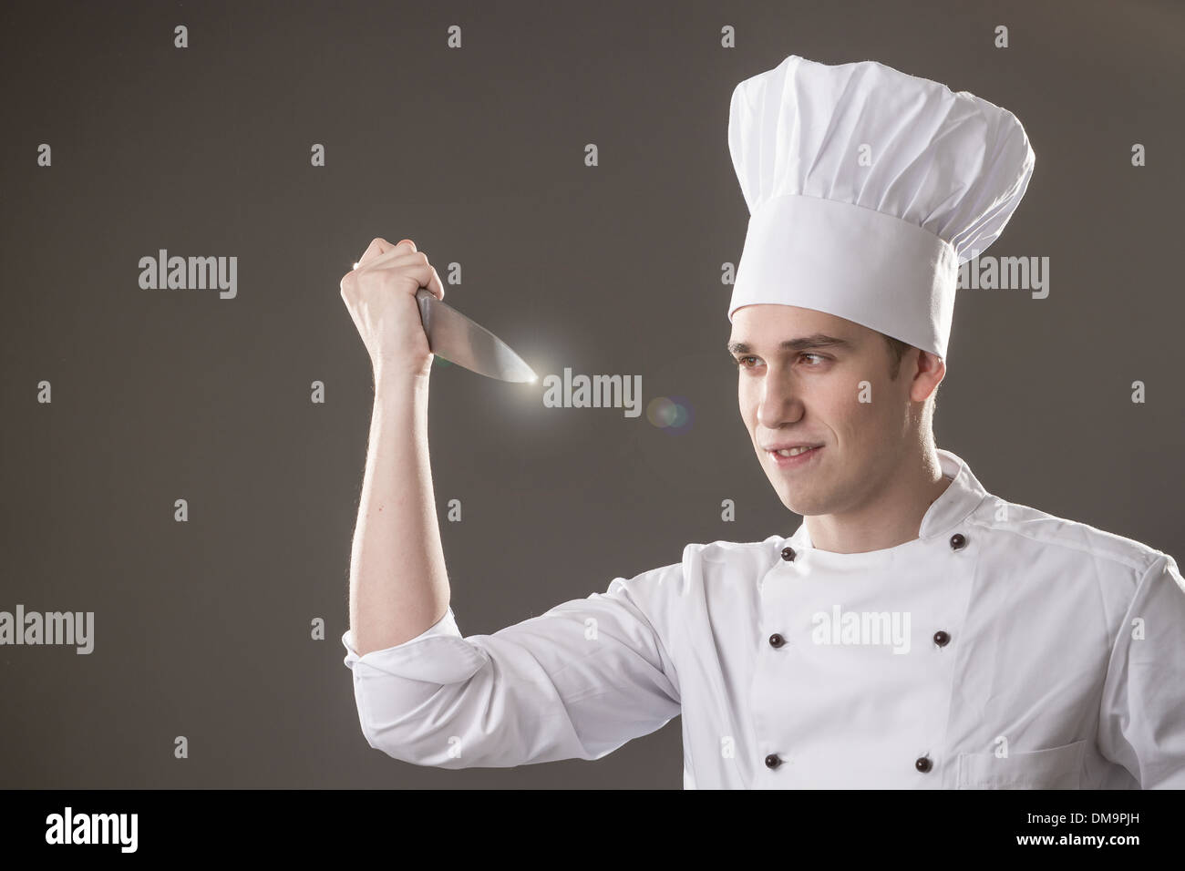 Portrait of smiling chef with in hand isolated on grey background Stock Photo