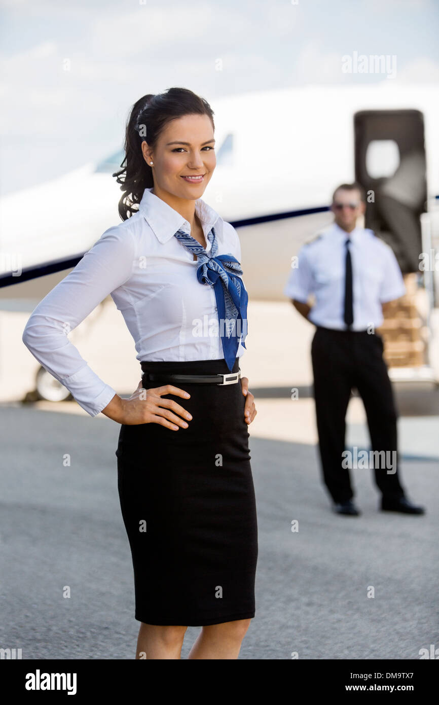 Confident Airhostess With Hands On Hip Smiling At Airport Termin - Stock Image